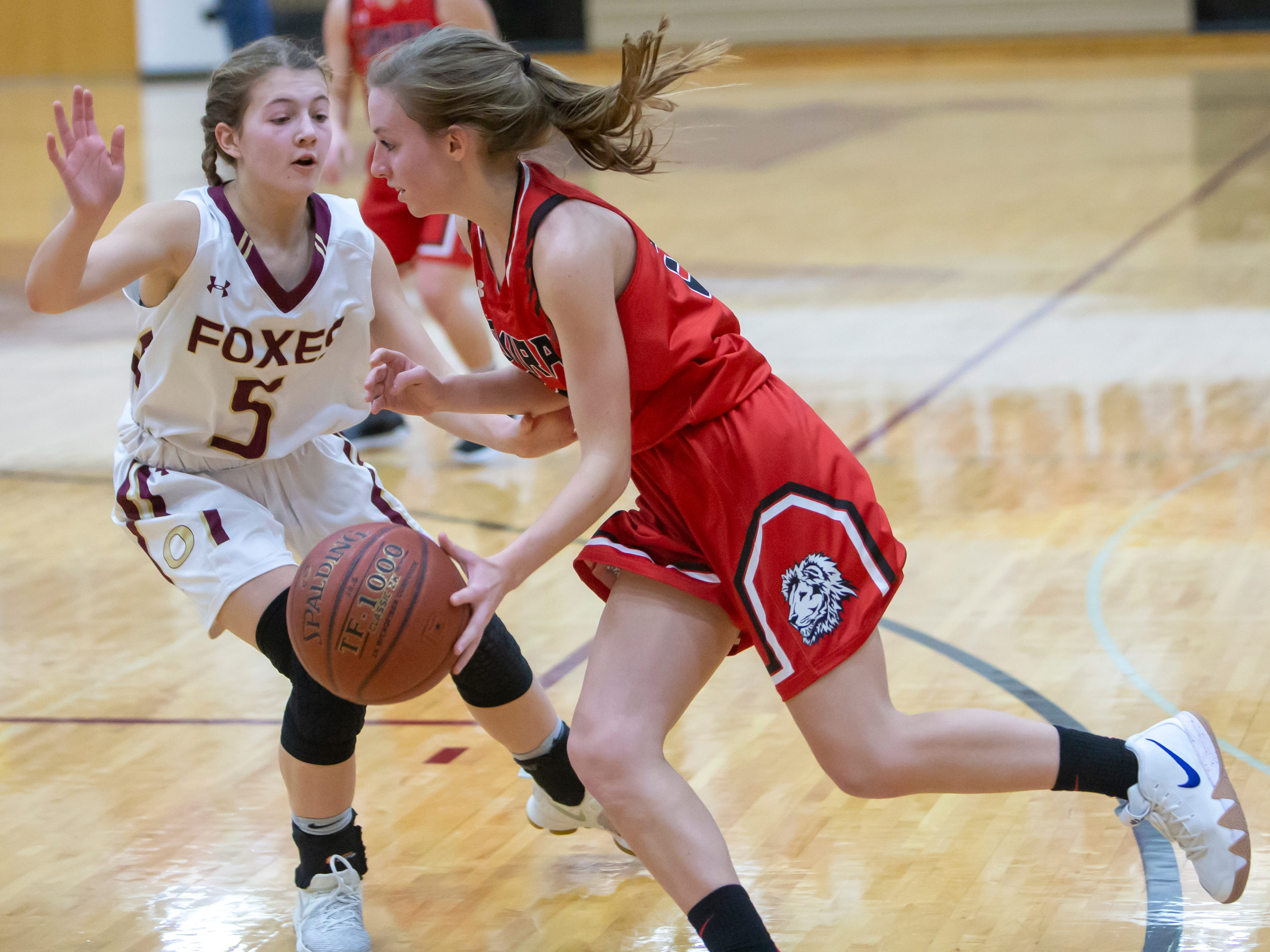 Lomira's Kail Brath drives the to the basket around Omro's Hannah Fedderly at Omro High School on Friday, December 14, 2018.