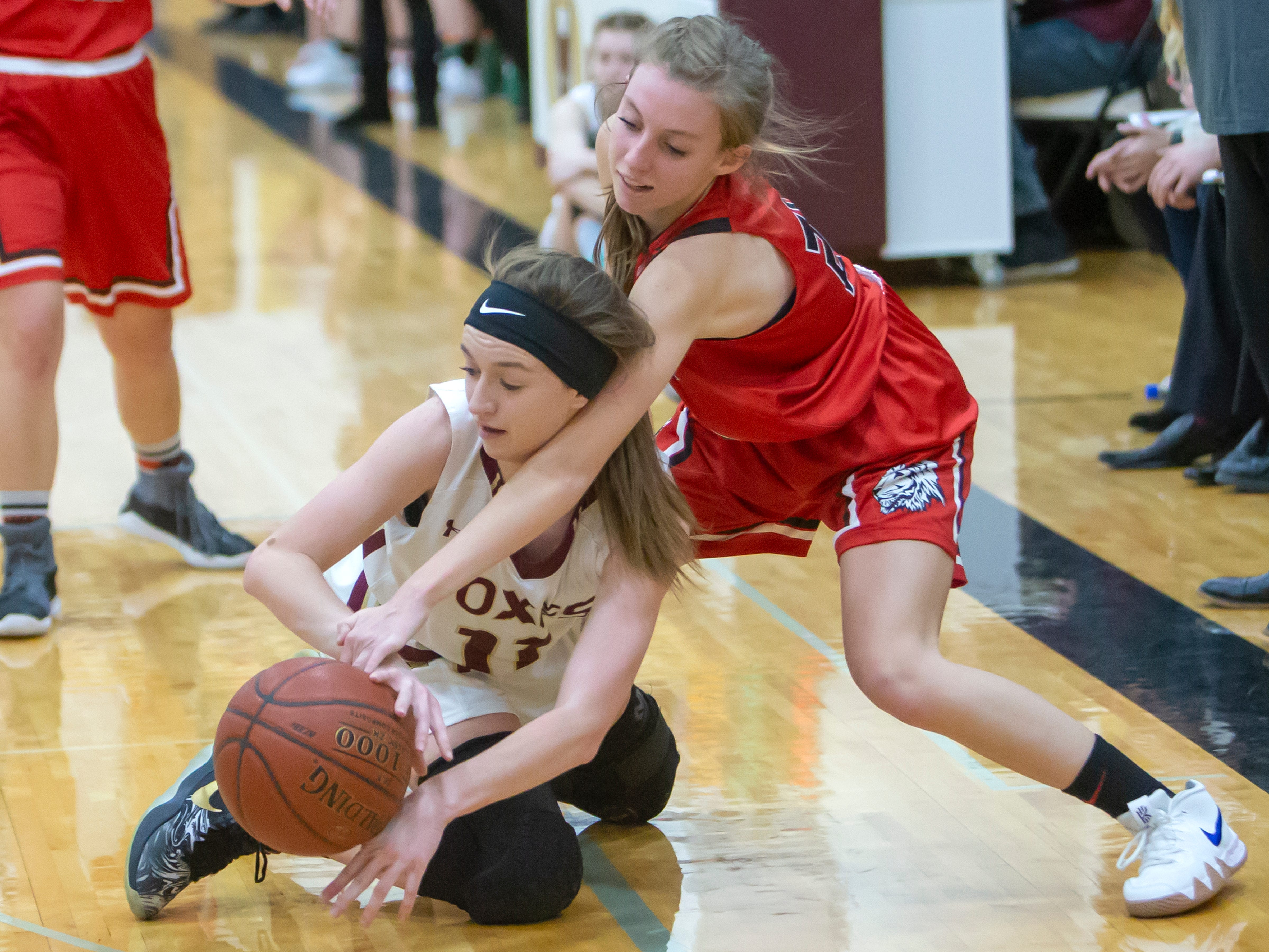 Lomira's Kailin Brath attempts to break the ball from Omro's Danycka Milis at Omro High School on Friday, December 14, 2018.