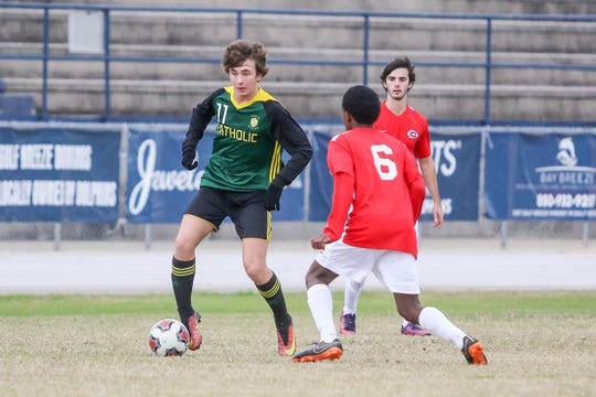Pensacola Catholic's Hobie Davenport (11) works to get the ball around Clinton's Jarrean Hoskins (6) at Gulf Breeze High School on Saturday, December 15, 2018.