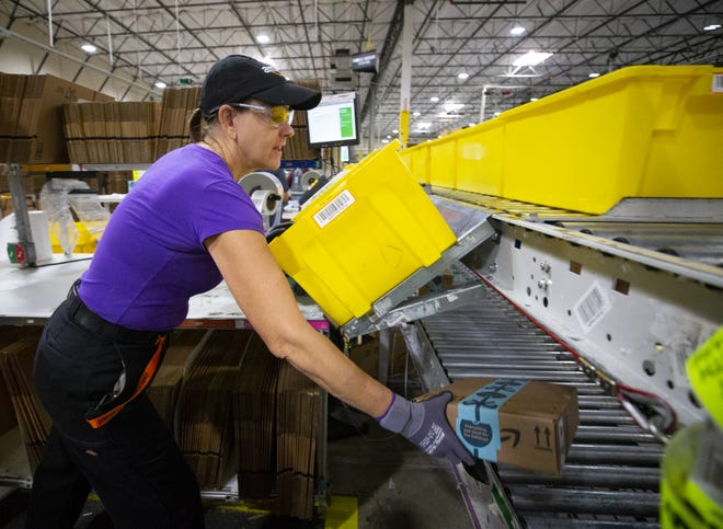 Marney Redmond, packing associate at Amazon Fulfillment Center in Phoenix, is busy filling orders on Dec. 14, 2018.
