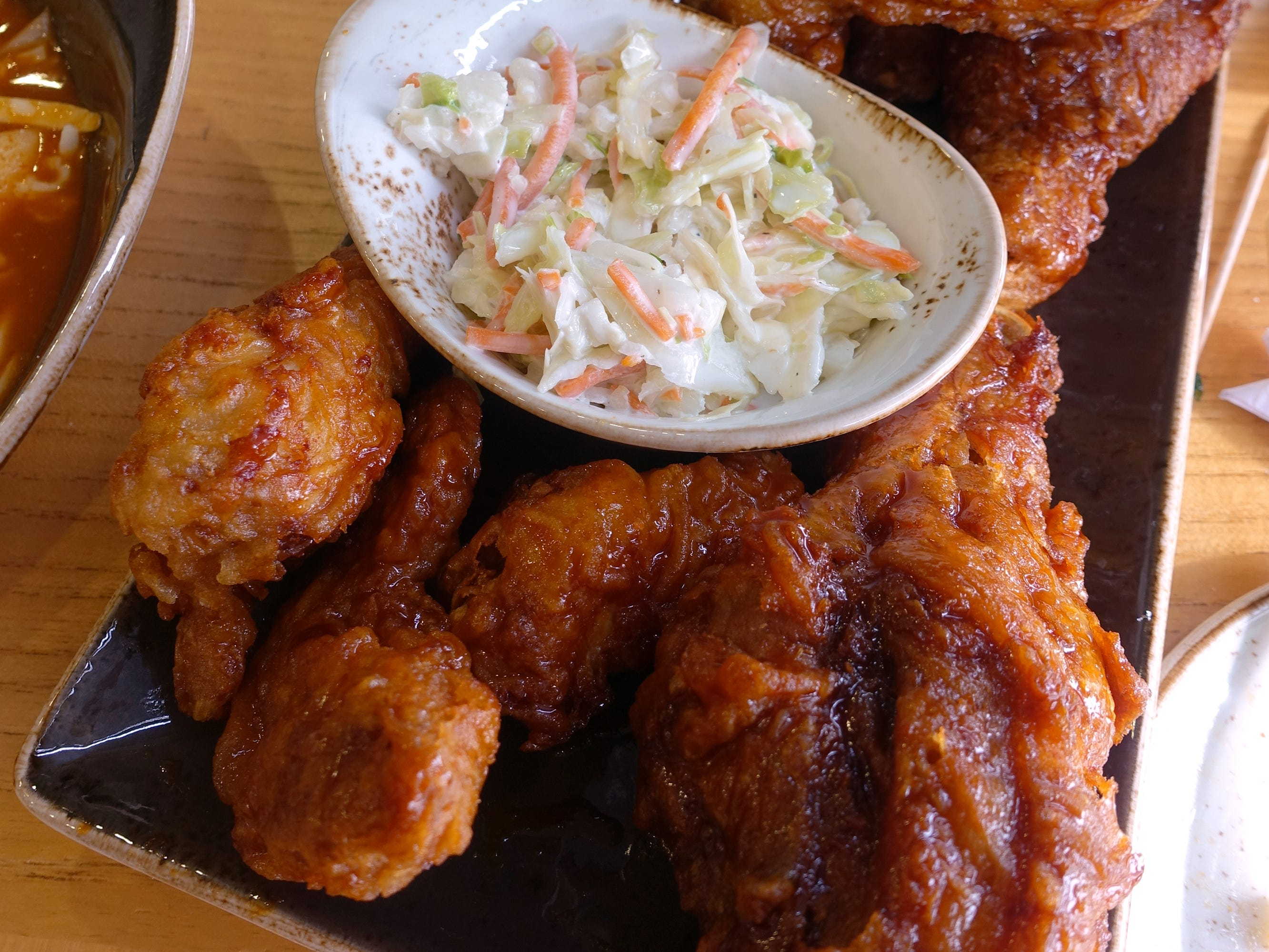 Spicy fried chicken (foreground) and garlic soy fried chicken (background) with coleslaw at Bonchon in Tempe.