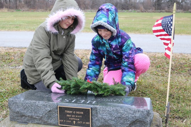 Paige and Gabby Sims place a wreath at the grave site of their grandfather, Terry Heise, a local Navy veteran who served in Vietnam. The effort was part of the Wreaths Across American ceremony held at Riverview Cemetery in Port Clinton on Saturday.