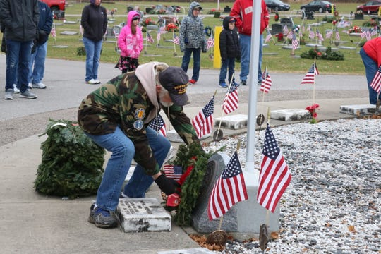 A local veteran who served in the U.S. Marine Corps places a wreath as part of the Wreaths Across American ceremony held at Riverview Cemetery in Port Clinton on Saturday.