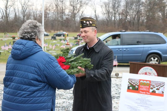 Local veteran Bert Fall, who served as master of ceremonies for the Wreaths Across America event at Riverview Cemetery in Port Clinton, hands out wreaths to place on Saturday morning.