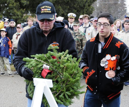 Bob Gardiner and his grandson Nicholas Borunda place a wreath honoring U.S. Army veterans during the Wreaths Across America event on Saturday, Dec. 15, 2018 at the St. Clair County Allied Veterans Cemetery.