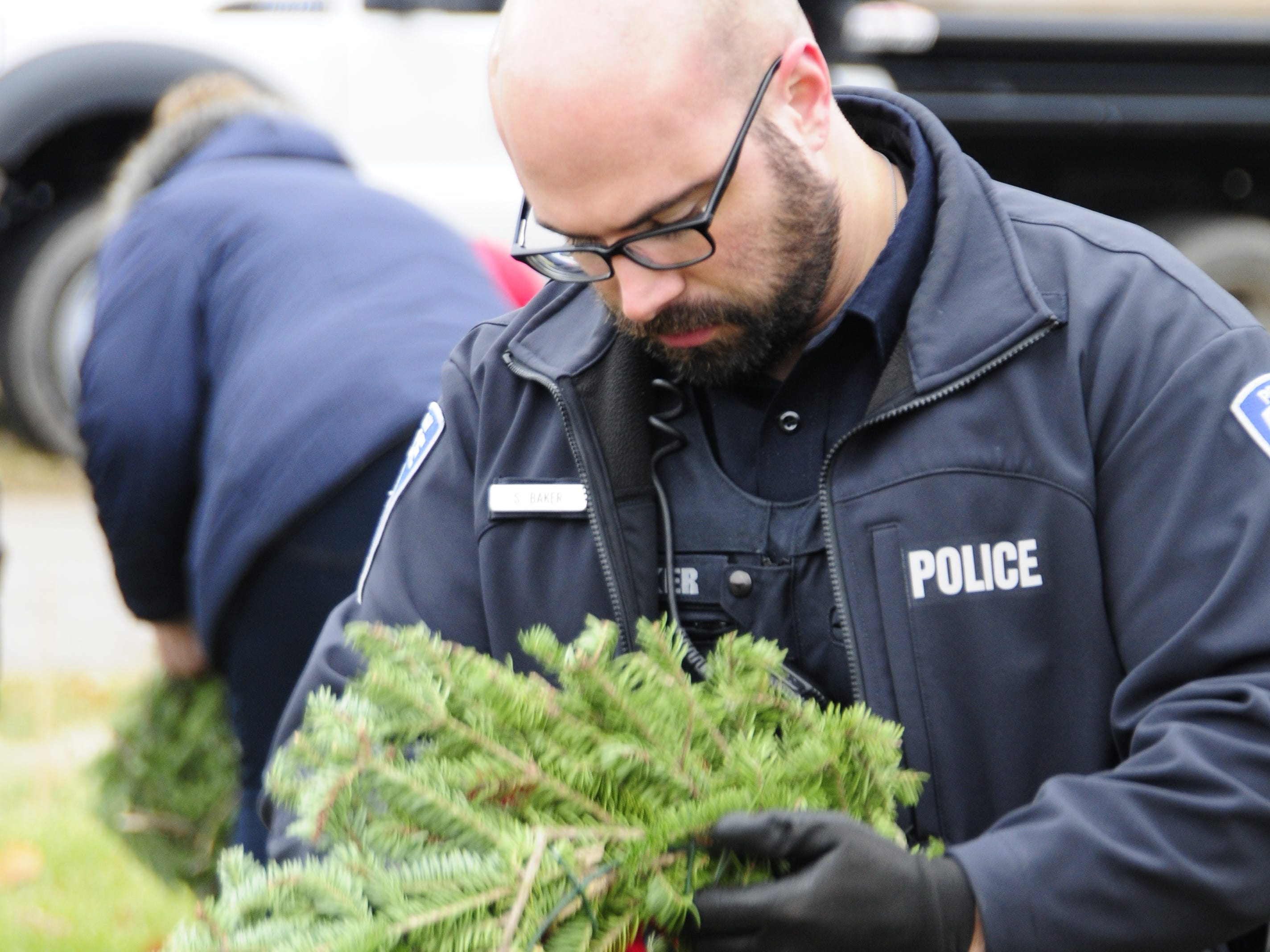 Port Huron Police Officer Sam Baker places a wreath during Wreaths Across America on Saturday, Dec. 15, 2018 at St. Clair County Allied Veterans Cemetery in Port Huron.