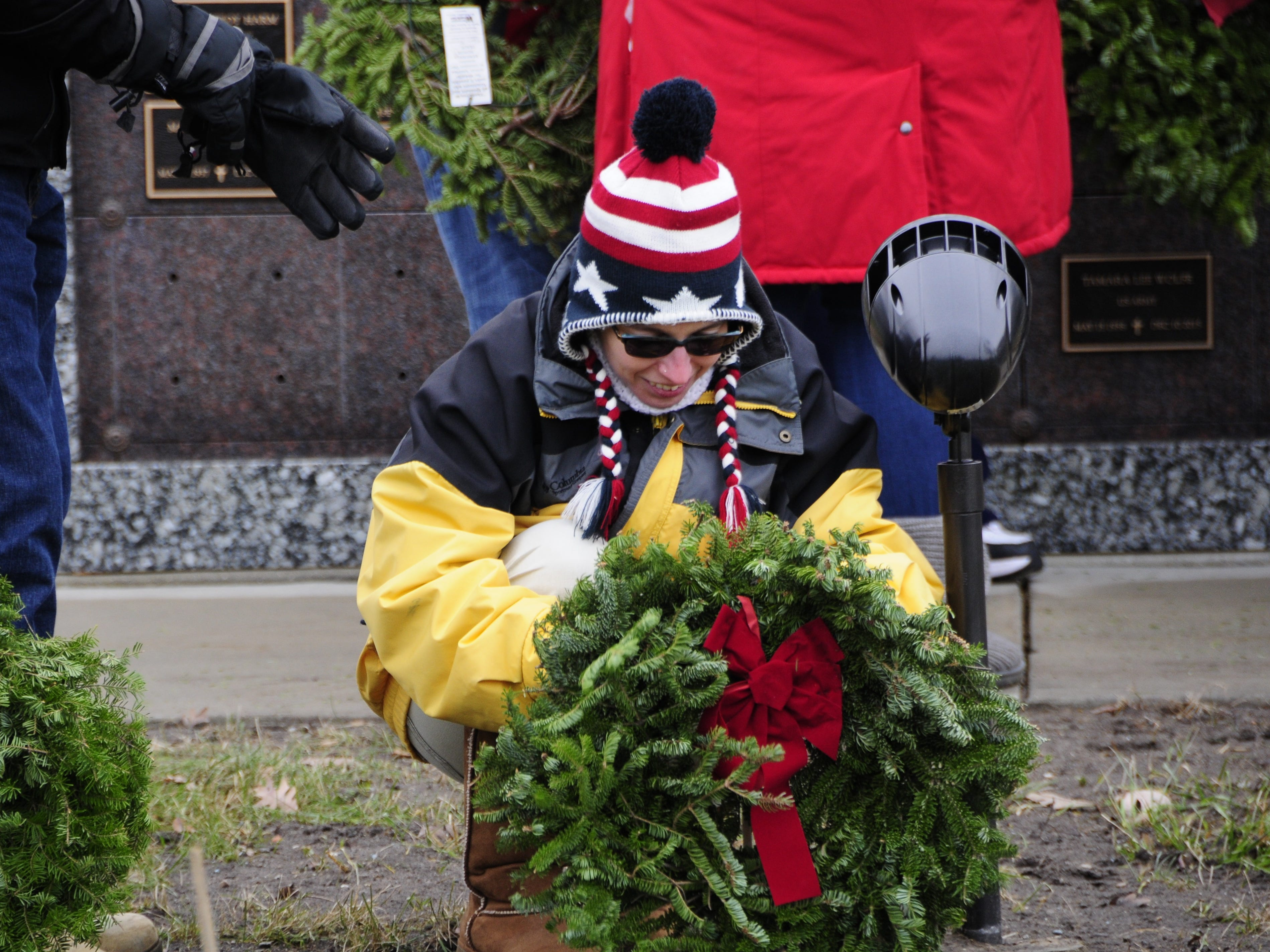 Nicole Routhier of Clyde Township places a wreath on a grave during the Wreaths Across America event on Saturday, Dec. 15, 2018 at the St. Clair County Allied Veterans Cemetery.
