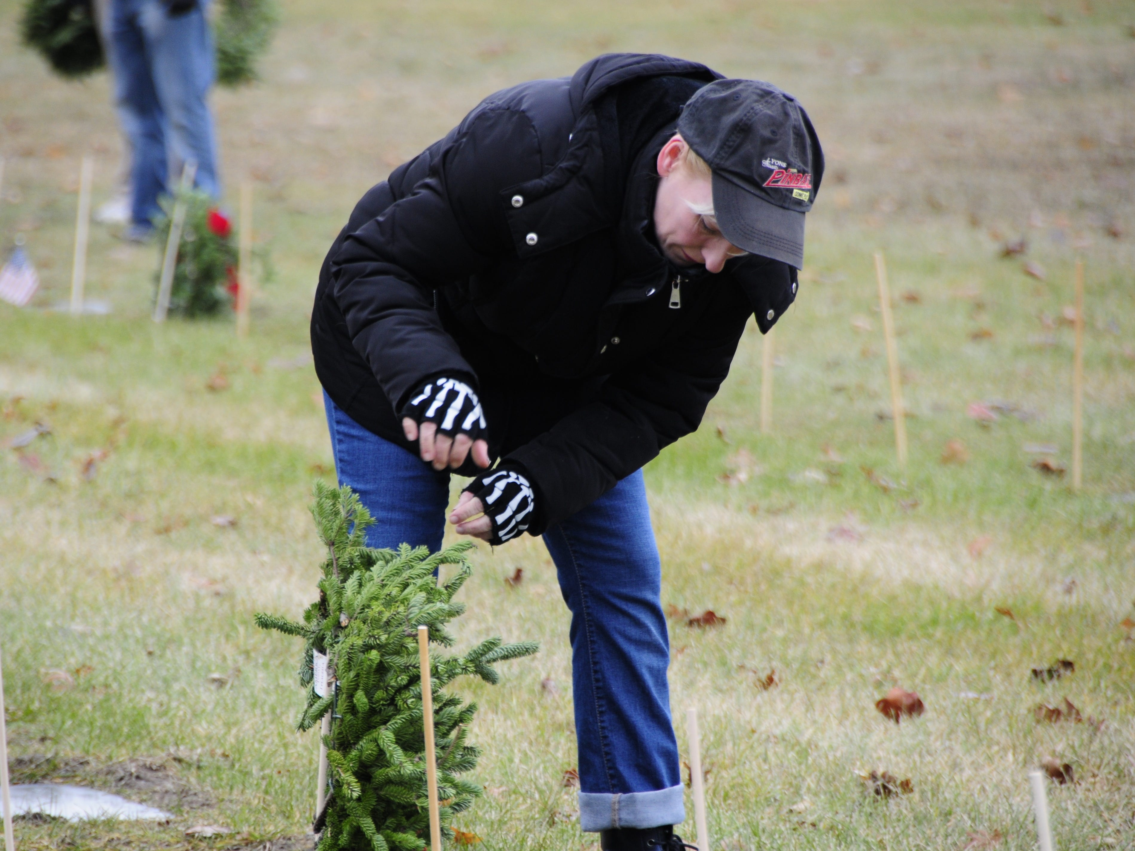 Heather Scholfield places a wreath during Wreaths Across America on Saturday, Dec. 15, 2018 at St. Clair County Allied Veterans Cemetery in Port Huron.