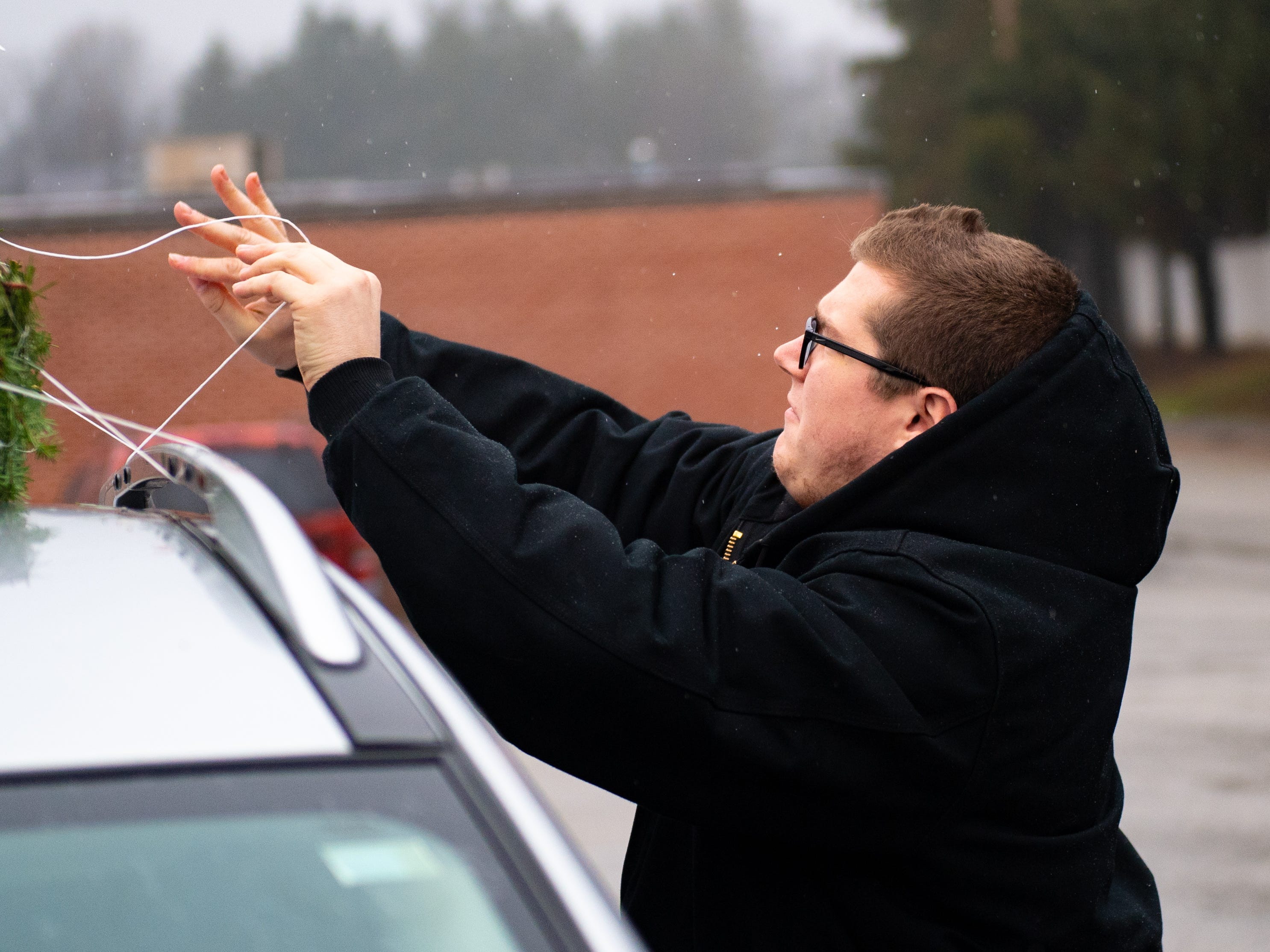 After the tree is wrapped up, volunteers, like Logan Arnold, put it on to top of customers' cars, December 15, 2018.