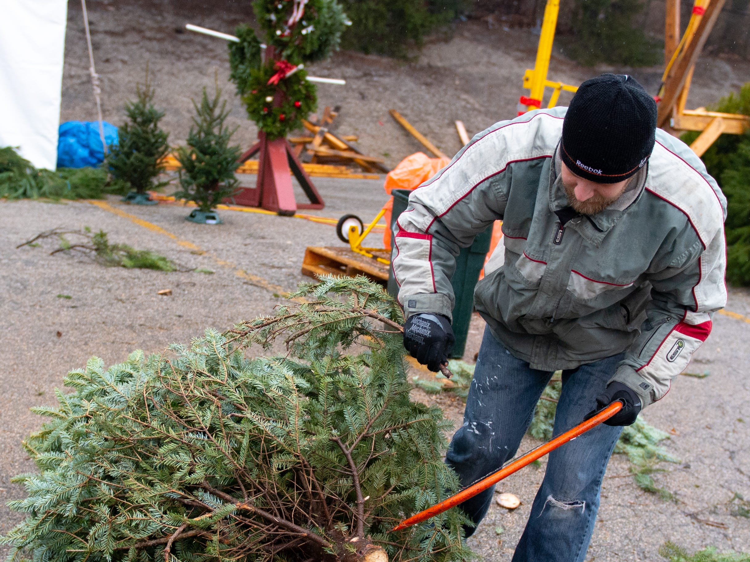 Volunteer Cody Miller saws off the lowest branches of a tree at the annual Christmas Tree Sale, Saturday, December 15, 2018.