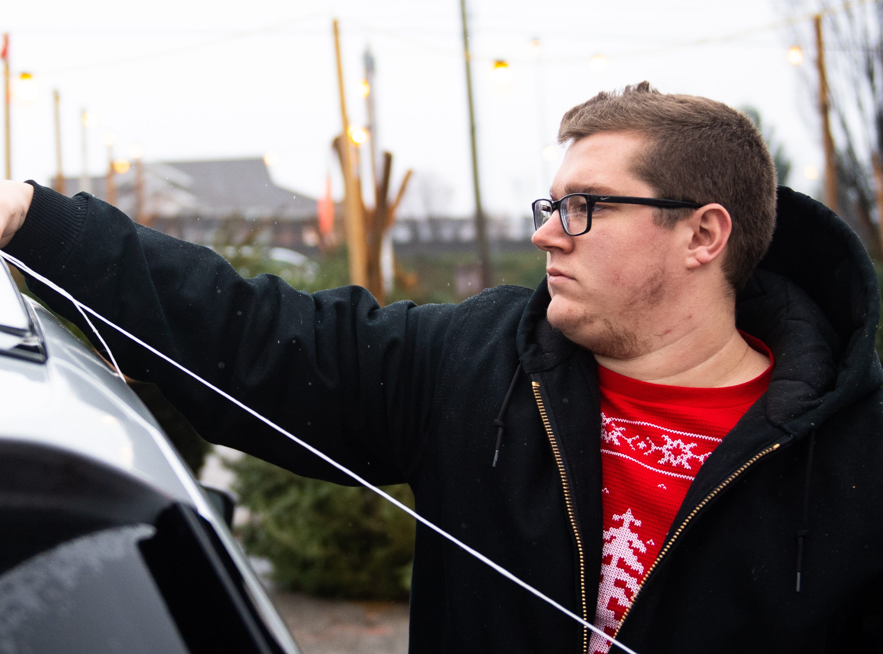 Volunteer Logan Arnold ties a tree to the top of a vehicle, Saturday, December 15, 2018.
