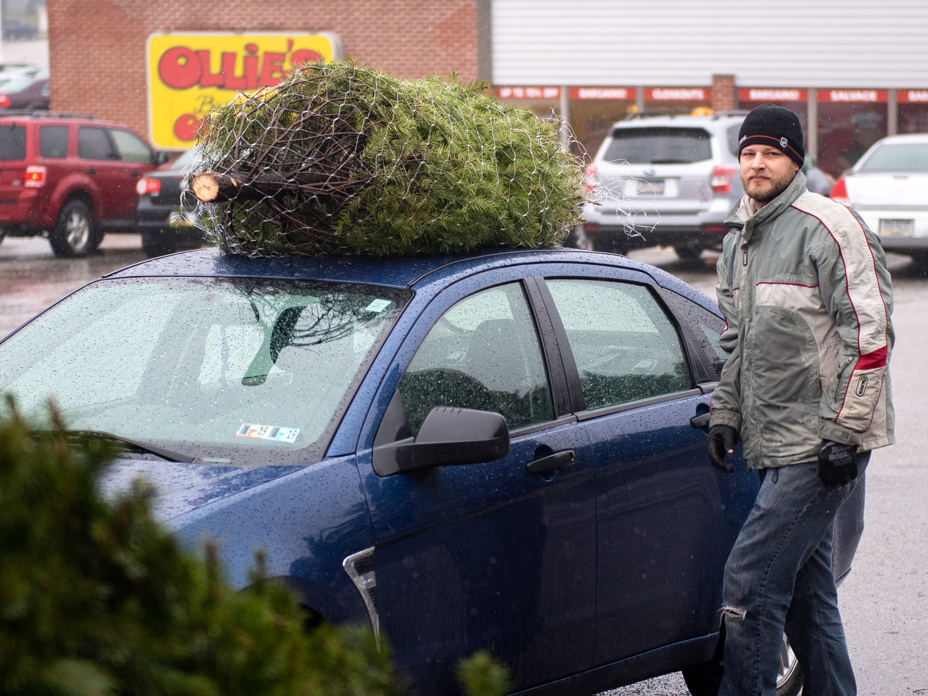Customers bring various vehicles to the lot get trees at the annual Christmas Tree Sale in the parking lot of Ollie's Bargain Outlet, Saturday, December 15, 2018.