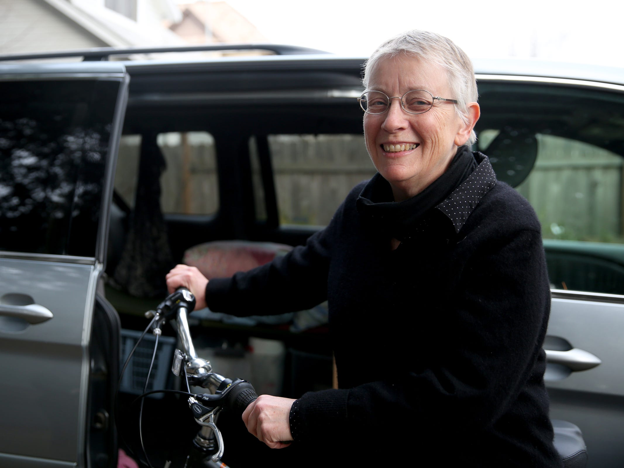 Jean Brougher stands will her bicycle and minivan which she will travel with as she volunteers at an animal shelter near Paradise, California following wildfires. Photographed at Brougher's home in Salem on Friday, Dec. 14, 2018.