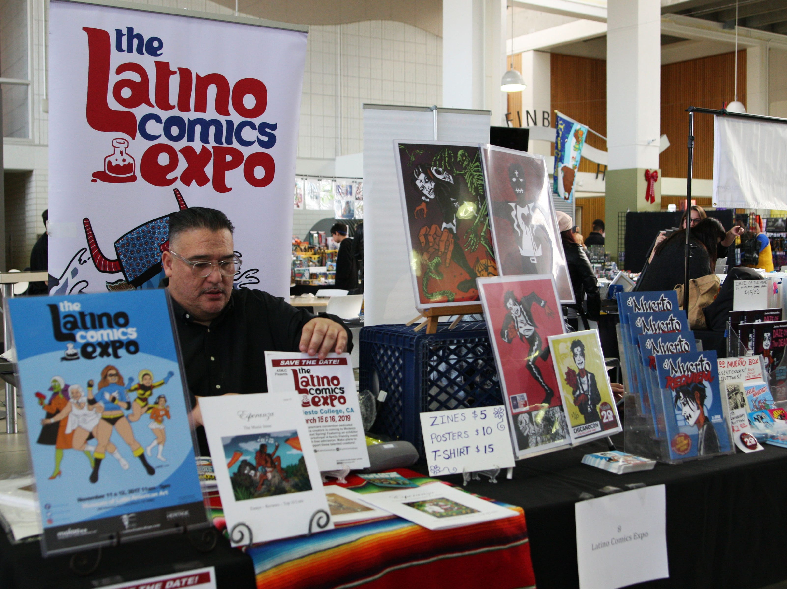 """Ricardo Padilla adjusts a sign advertising the next Latino Comics Expo. Padilla, a founder of the expo, said it is intended to showcase Latino artists and Latino-centric comics that give Latino children """"relatable content."""""""