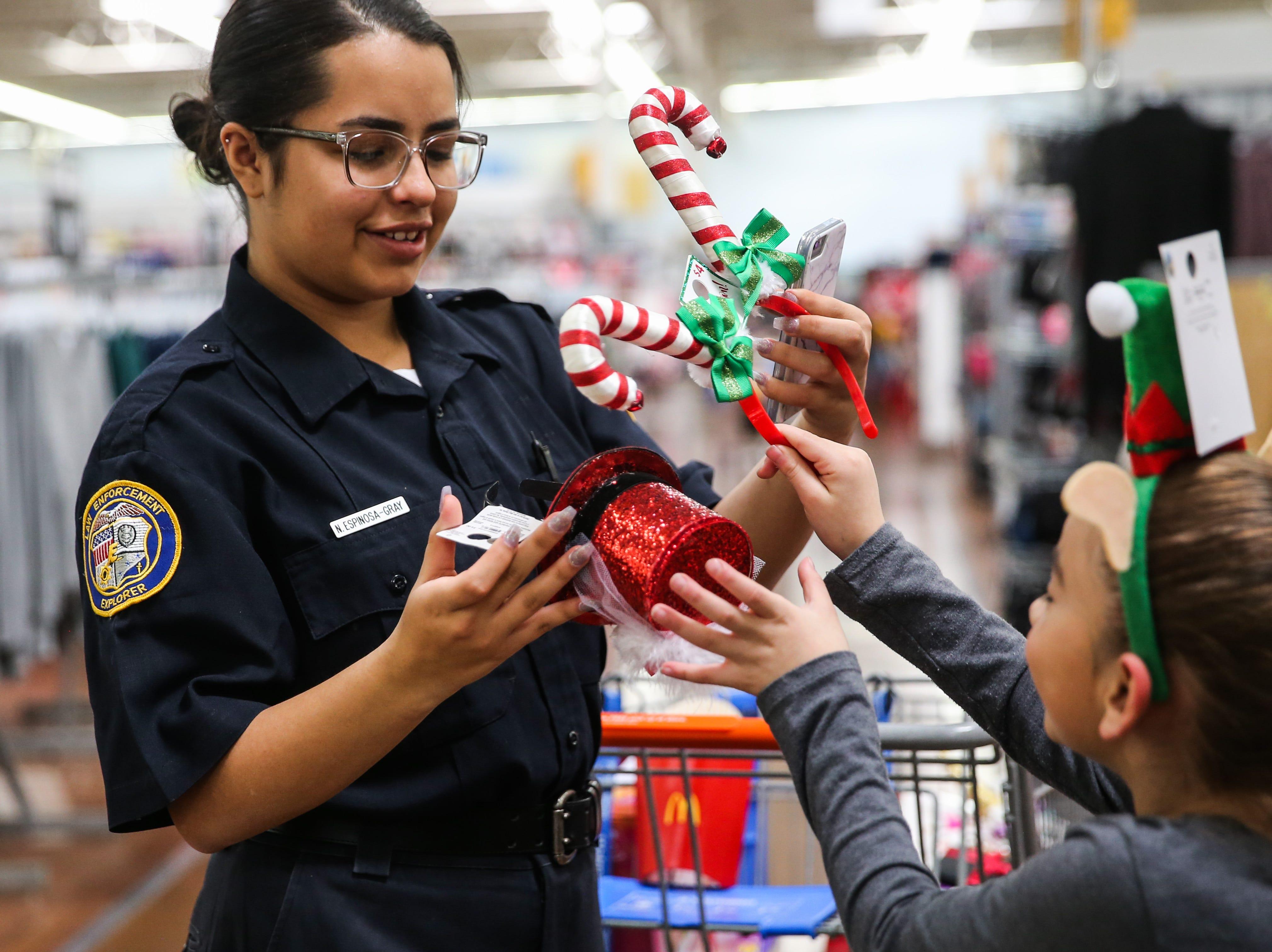 Nina Espinosa-Gray, Law Enforcement Explorer, picks a headband with Jasmin Delacruz, 8, while Delacruz's father participants in Shop with a Cop event Saturday, Dec. 15, 2018, at Walmart.