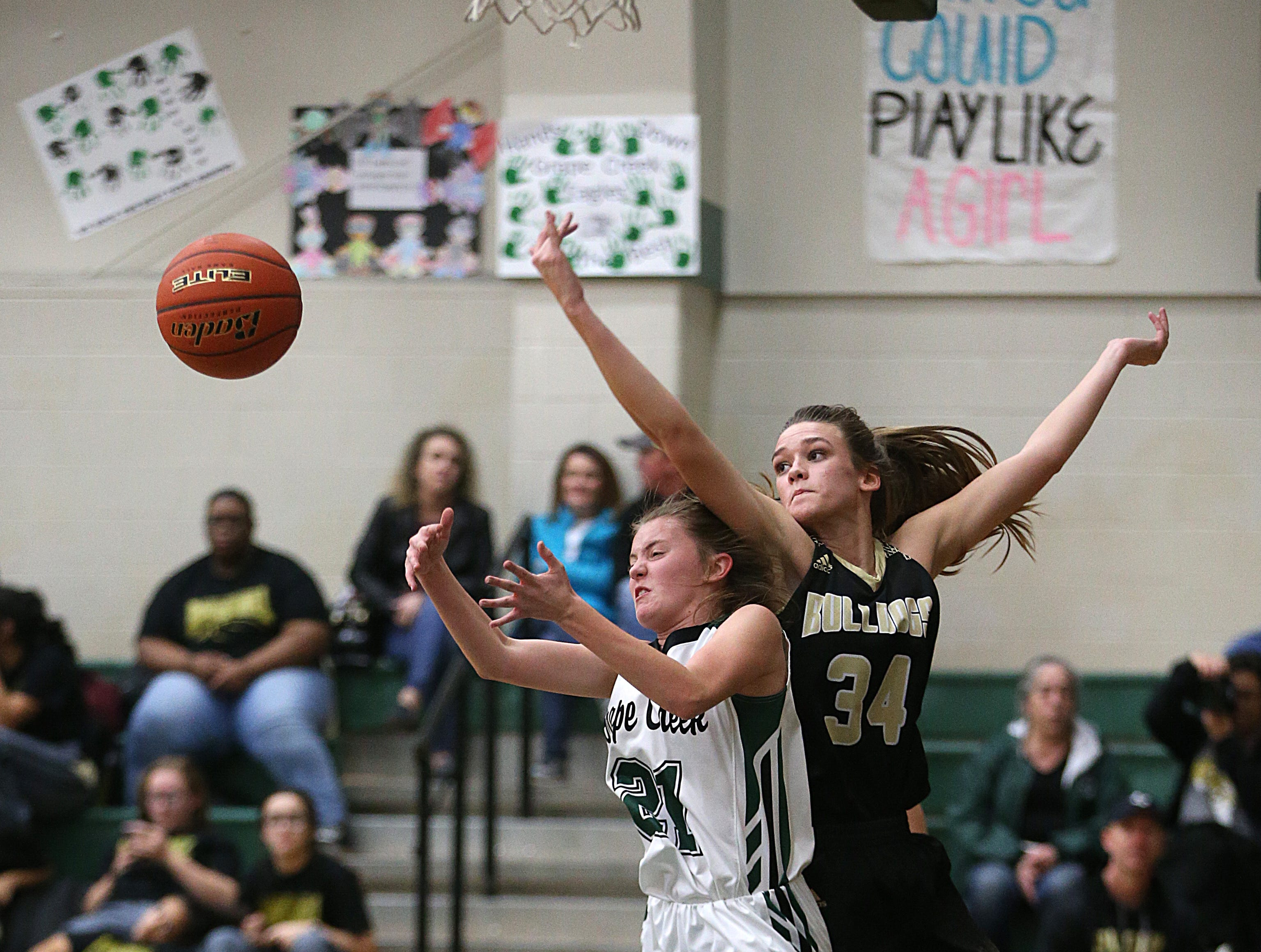 Grape Creek's Kimmy Salisbury (#21) misses a shot as Brady's Whitney Everett (#34) tries to recover it Friday, Dec. 14, 2018 during their game in Grape Creek. Brady won 48 to 28.