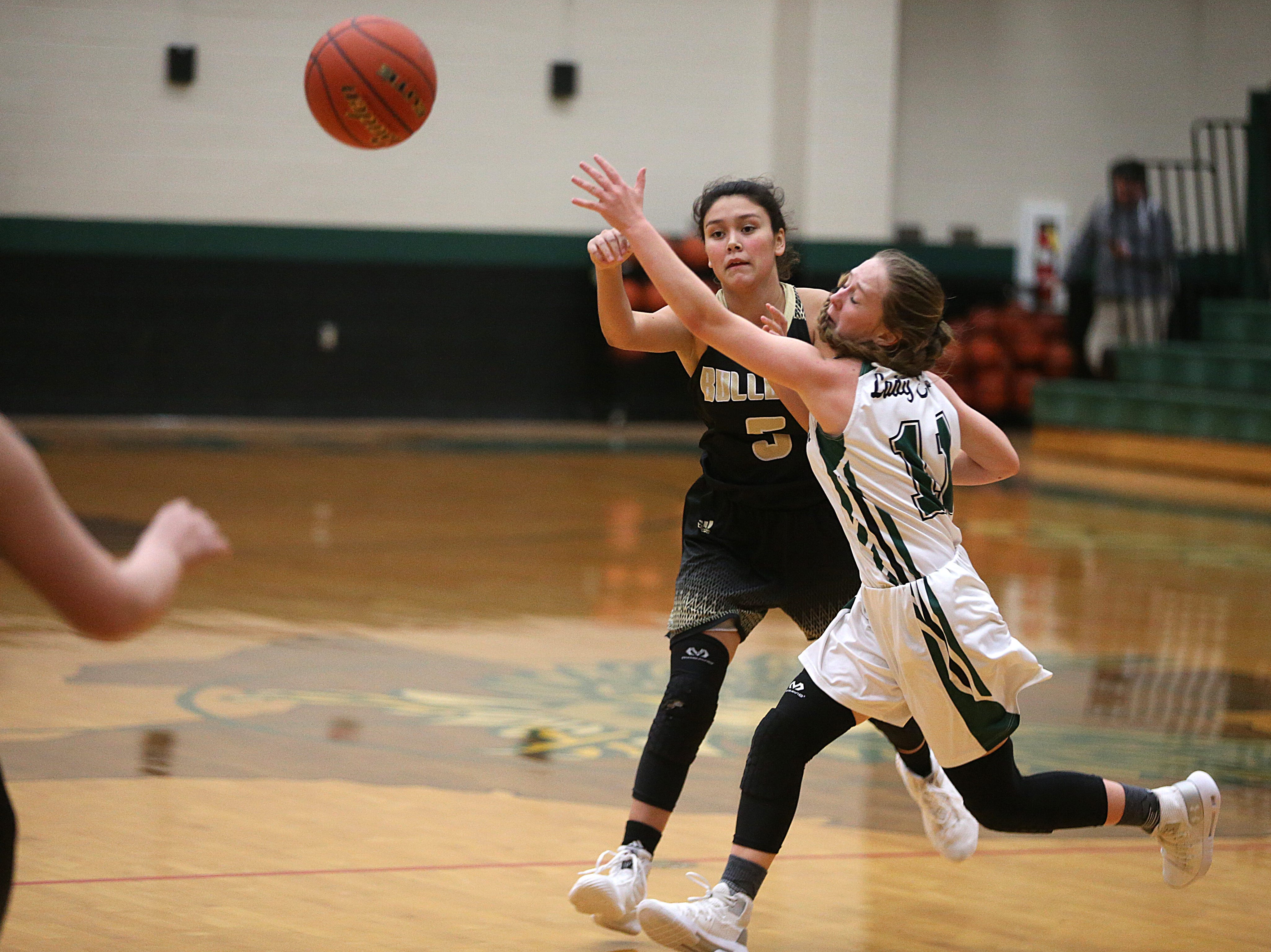 Brady's Nina Delafuente (#5) passes to a teammate as Grape Creek's Taigon Rivers (#11) tries to block Friday, Dec. 14, 2018 during their game in Grape Creek. Brady won 48 to 28.