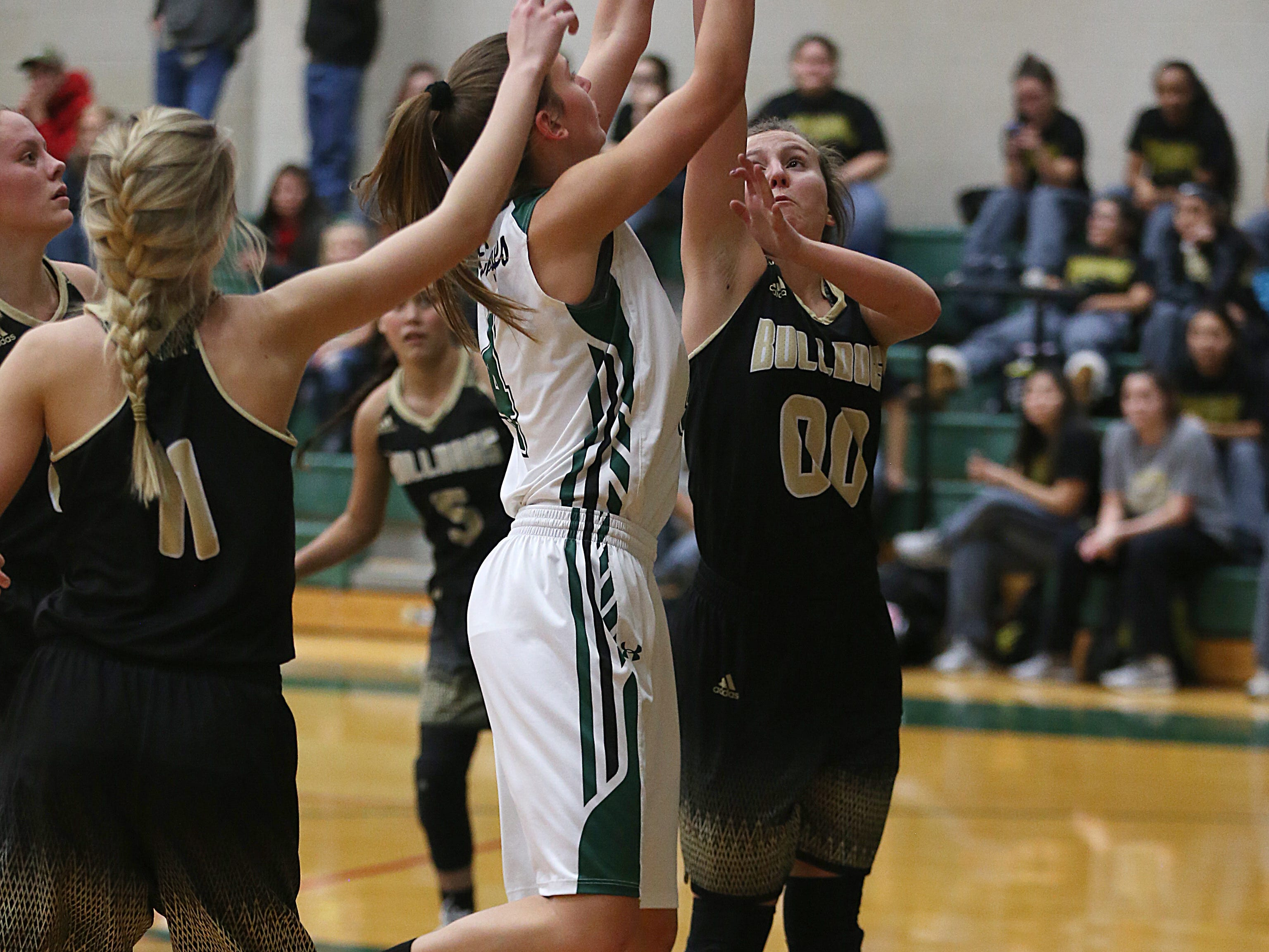 Grape Creek's Rachel Porter (#4) shoots for a basket as Brady's Lacy Cox (#4) tries to block Friday, Dec. 14, 2018 during their game in Grape Creek. Brady won 48 to 28.