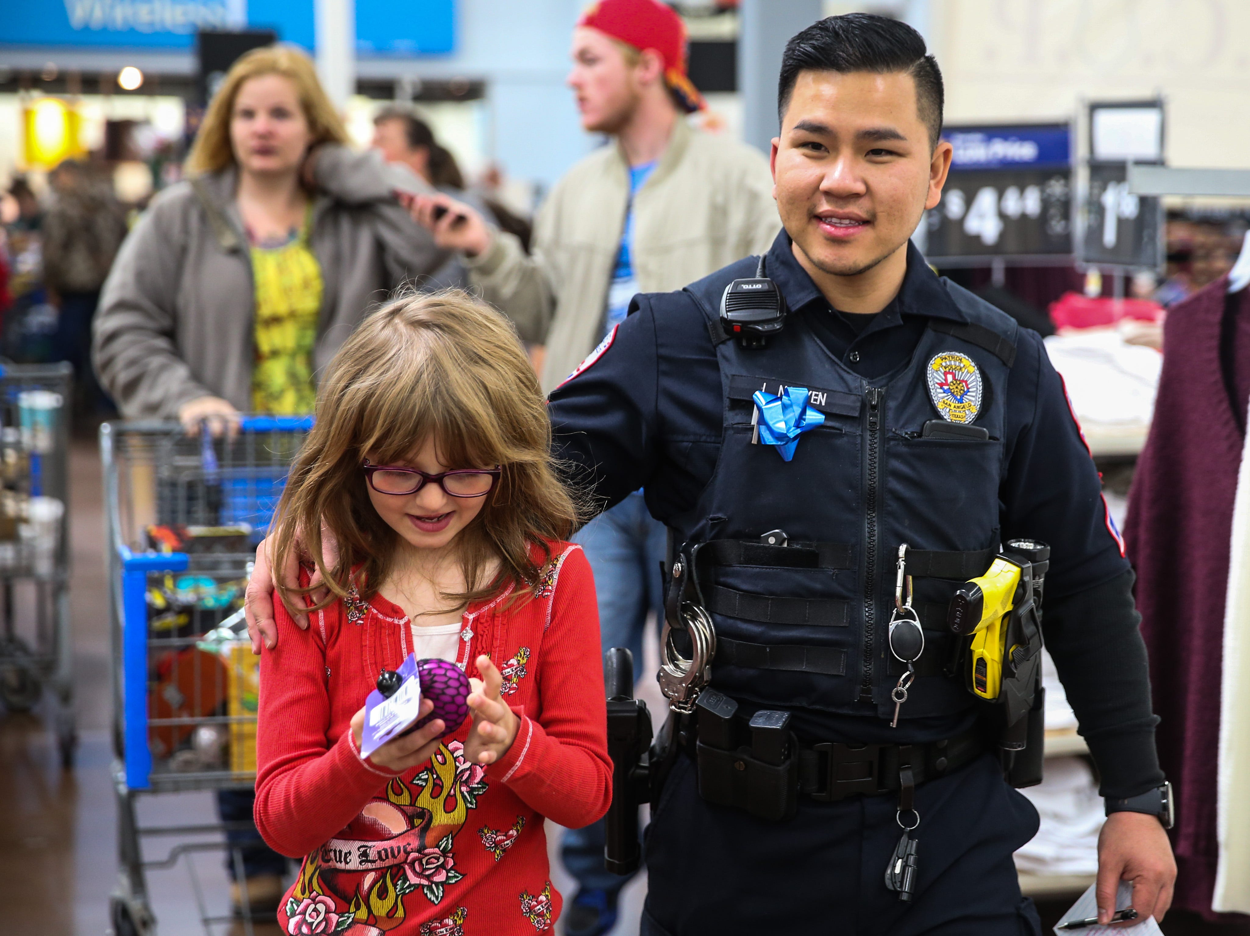 San Angelo Police officer Long Nguyen shops for gifts with Nicole Odell, 6, during Shop with a Cop event Saturday at Walmart.
