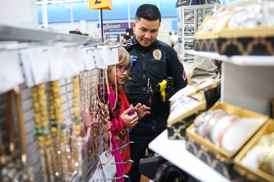 San Angelo Police officer Long Nguyen shops for gifts with Nicole Odell, 6, during Shop with a Cop event Saturday, Dec. 15, 2018, at Walmart.