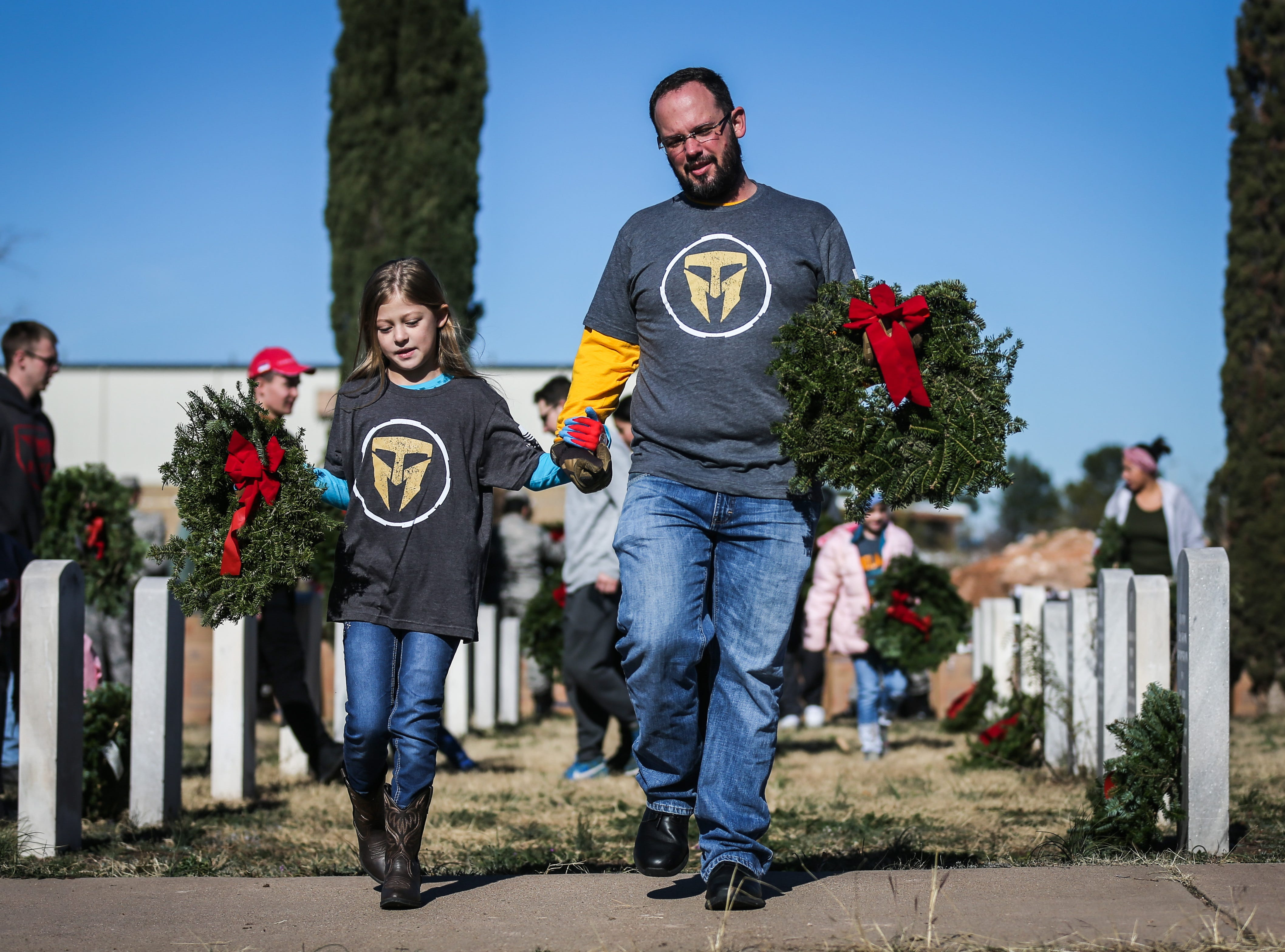Justin Bancroft and Lyla Bancroft, 9, carry wreaths to place on graves during Wreaths Across America Saturday, Dec. 15, 2018, at Belvedere Memorial Park.