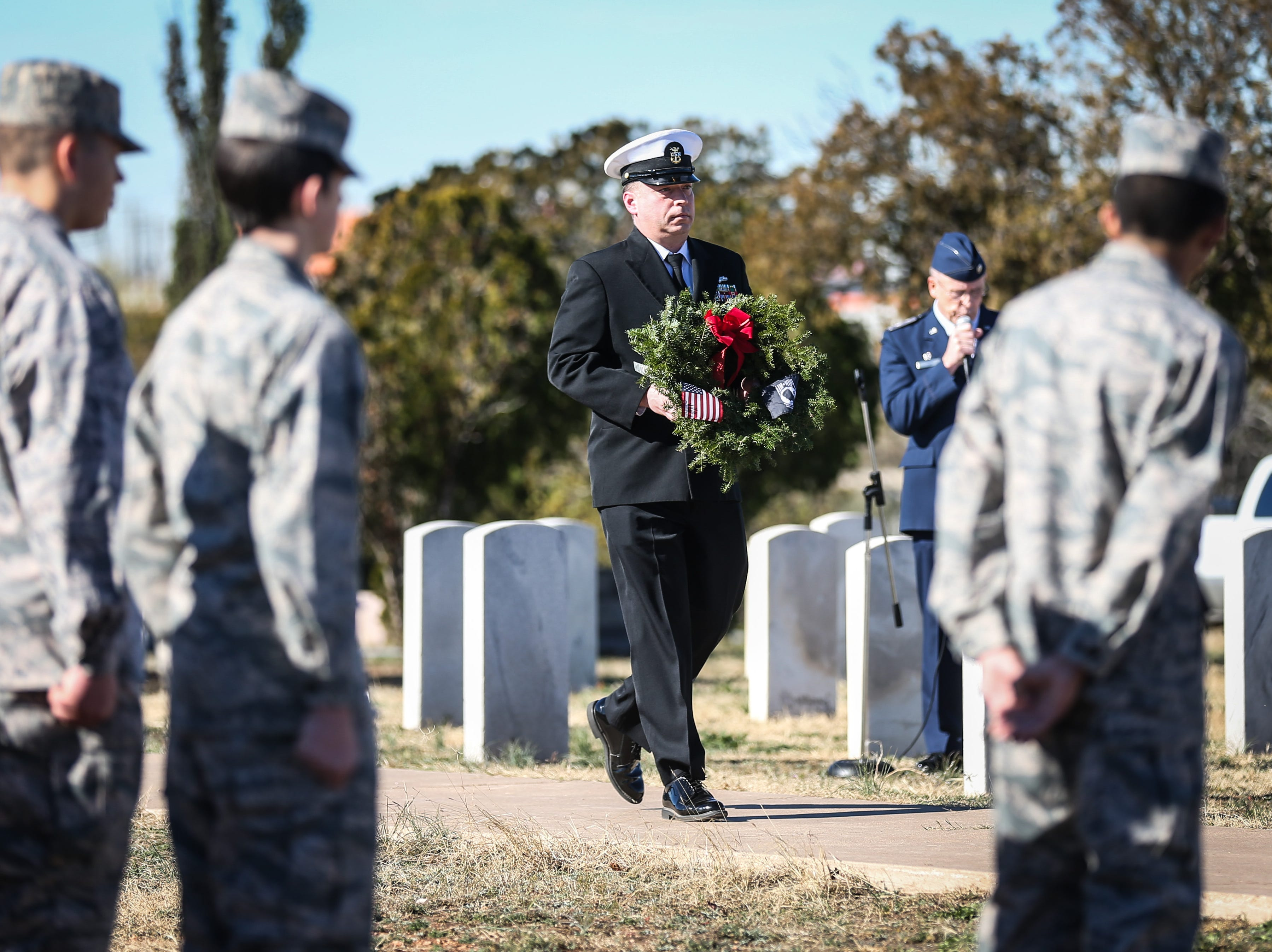 Navy Master Chief Petty Officer Joe Reynold walks up with a ceremonial wreath during the Wreaths Across America Saturday, Dec. 15, 2018, at Belvedere Memorial Park.