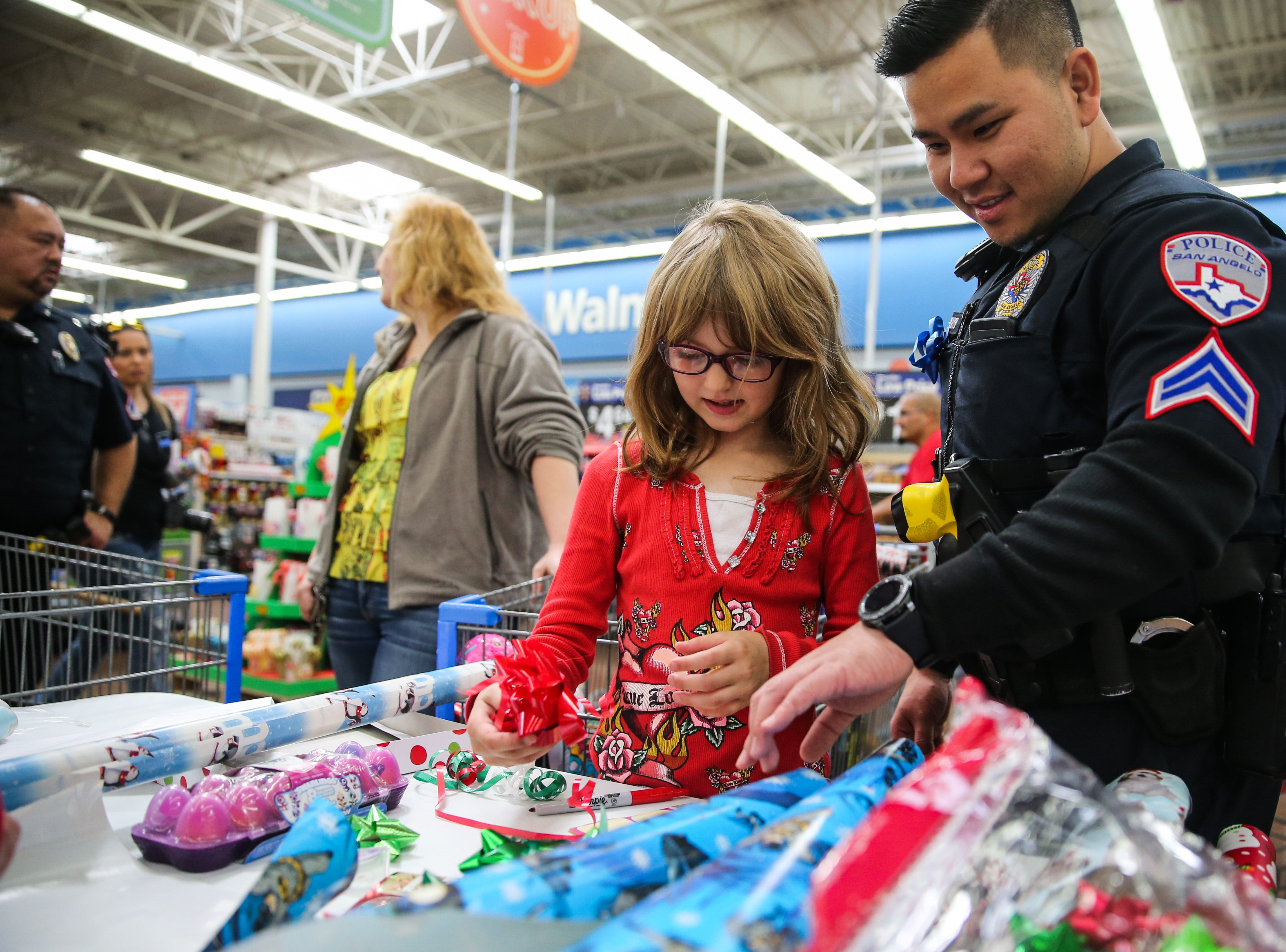 Nicole Odell, 6, and Officer Long Nguyen pick bows for the gifts during Shop with a Cop event Saturday, Dec. 15, 2018, at Walmart.
