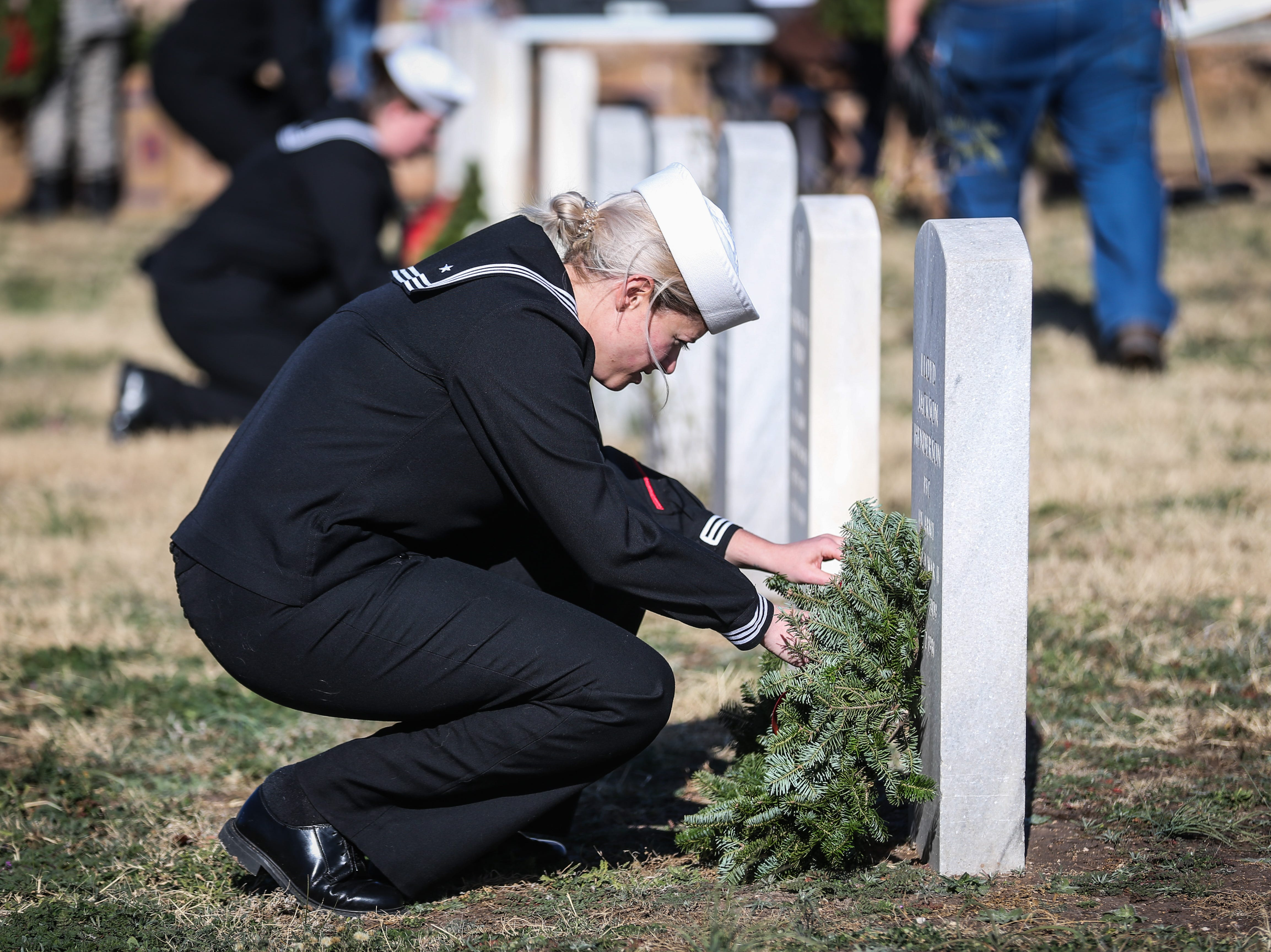 A participant places a wreath on a grave during Wreaths Across America Saturday, Dec. 15, 2018, at Belvedere Memorial Park.