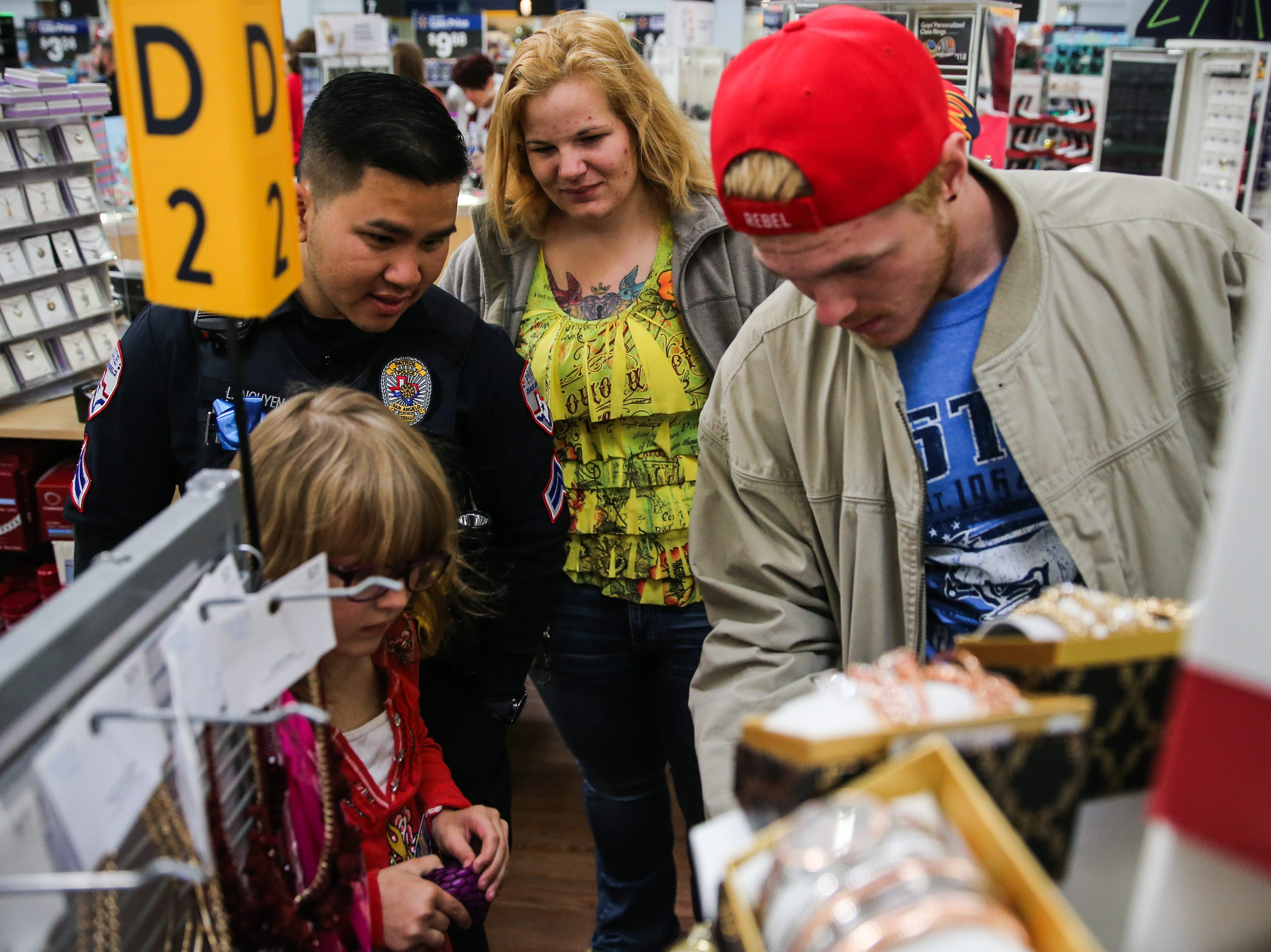 Officer Long Nguyen shops with Nicole Odell, 6, while she picks a gift for her stepfather, Brandon Wimberly, right, during Shop with a Cop event Saturday, Dec. 15, 2018, at Walmart.