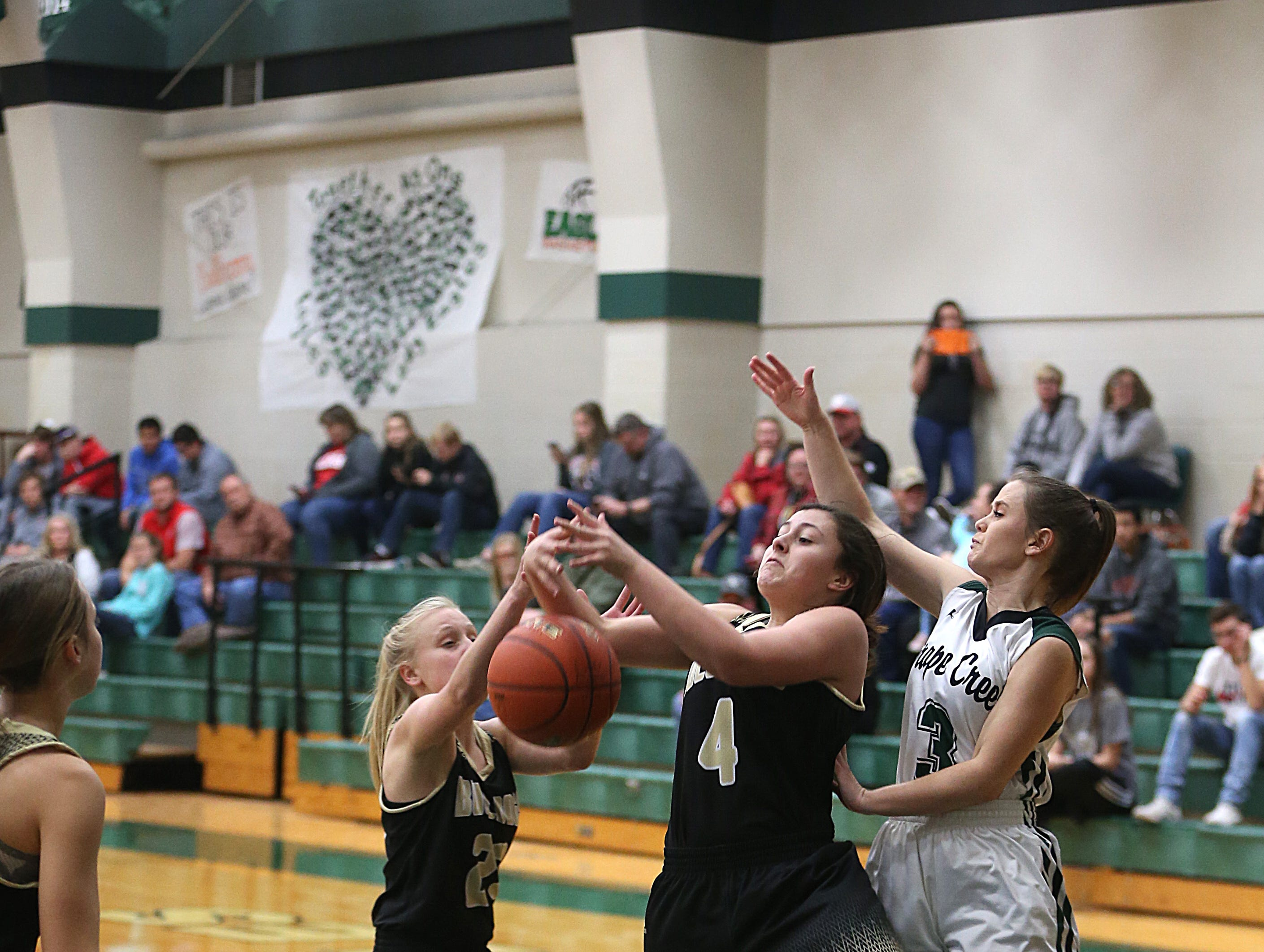 Brady's Shay McFarland (#4) and teammate Savanna Morton (#23) try to regain control of the ball before Grape Creek's McKenna Rivers Friday, Dec. 14, 2018 during their game in Grape Creek. Brady won 48 to 28.