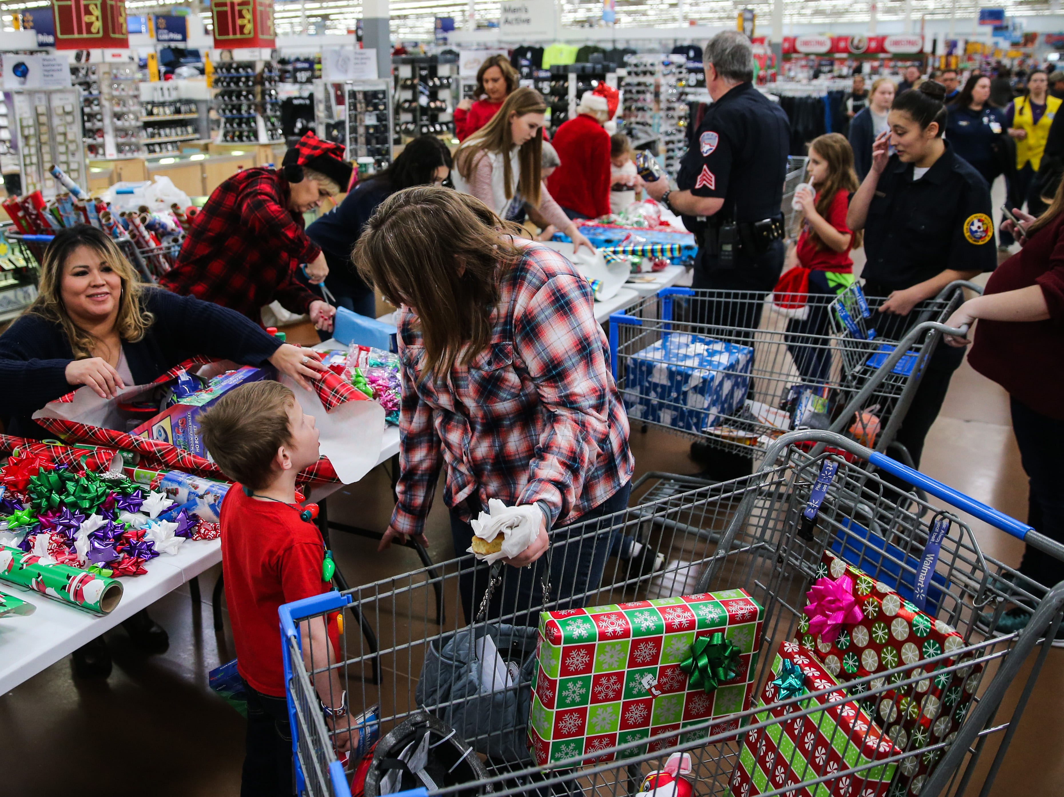 Participants have their gifts wrapped during Shop with a Cop event Saturday, Dec. 15, 2018, at Walmart.