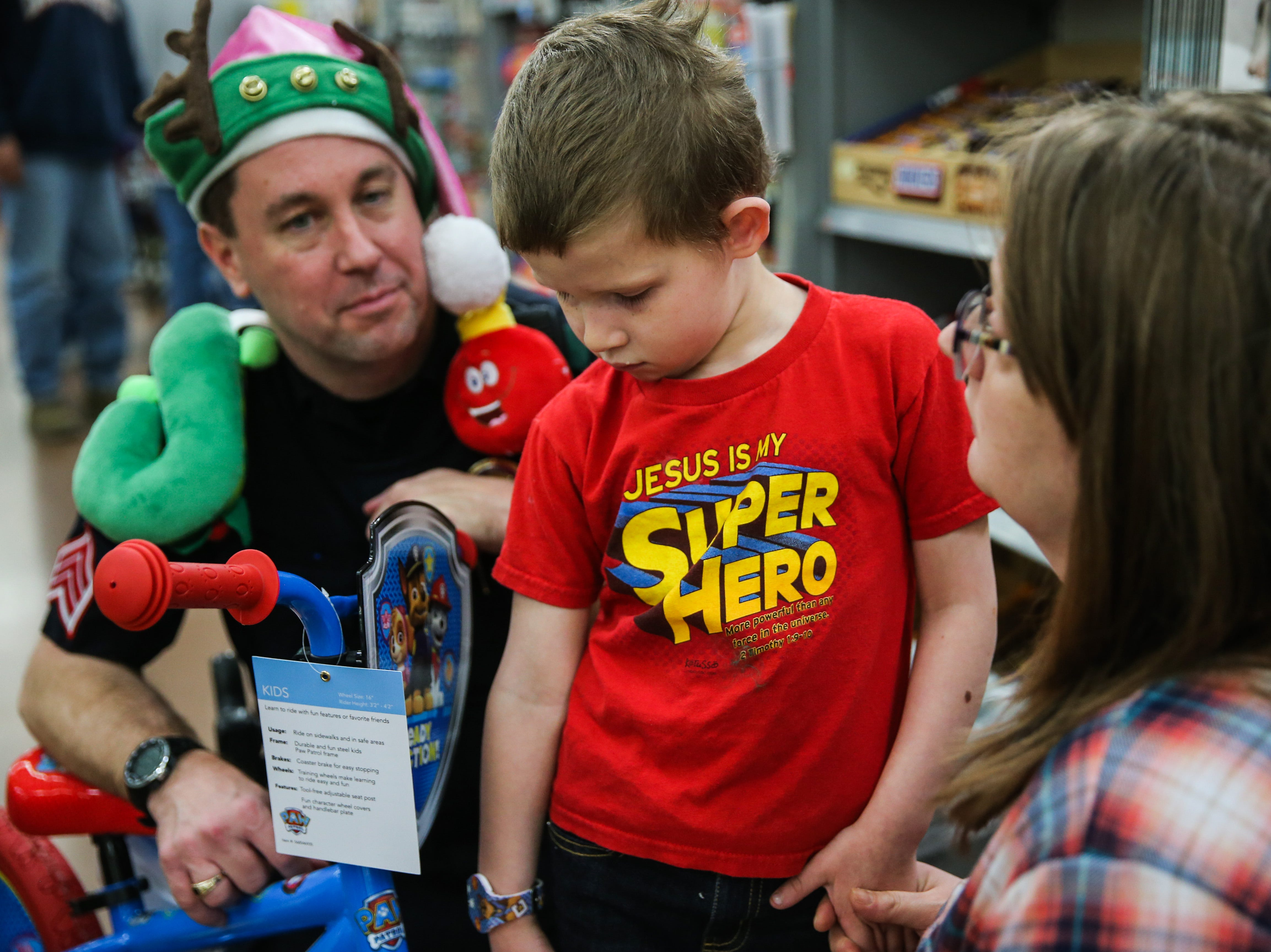 Sgt. Daniel Williams shops with Kyle Bible, 5, during Shop with a Cop event Saturday, Dec. 15, 2018, at Walmart.