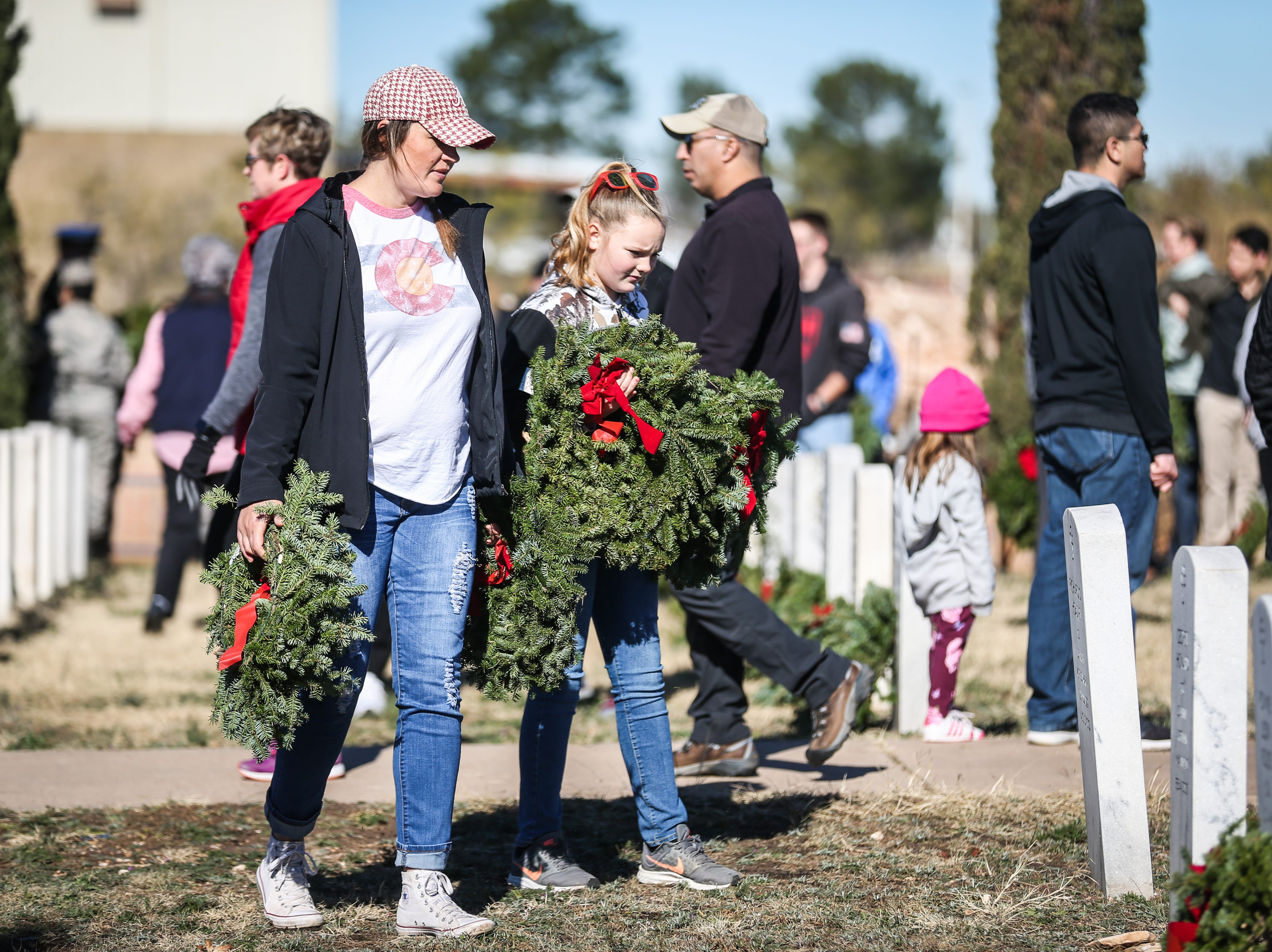 Participants carry wreaths to place on graves during Wreaths Across America Saturday, Dec. 15, 2018, at Belvedere Memorial Park.
