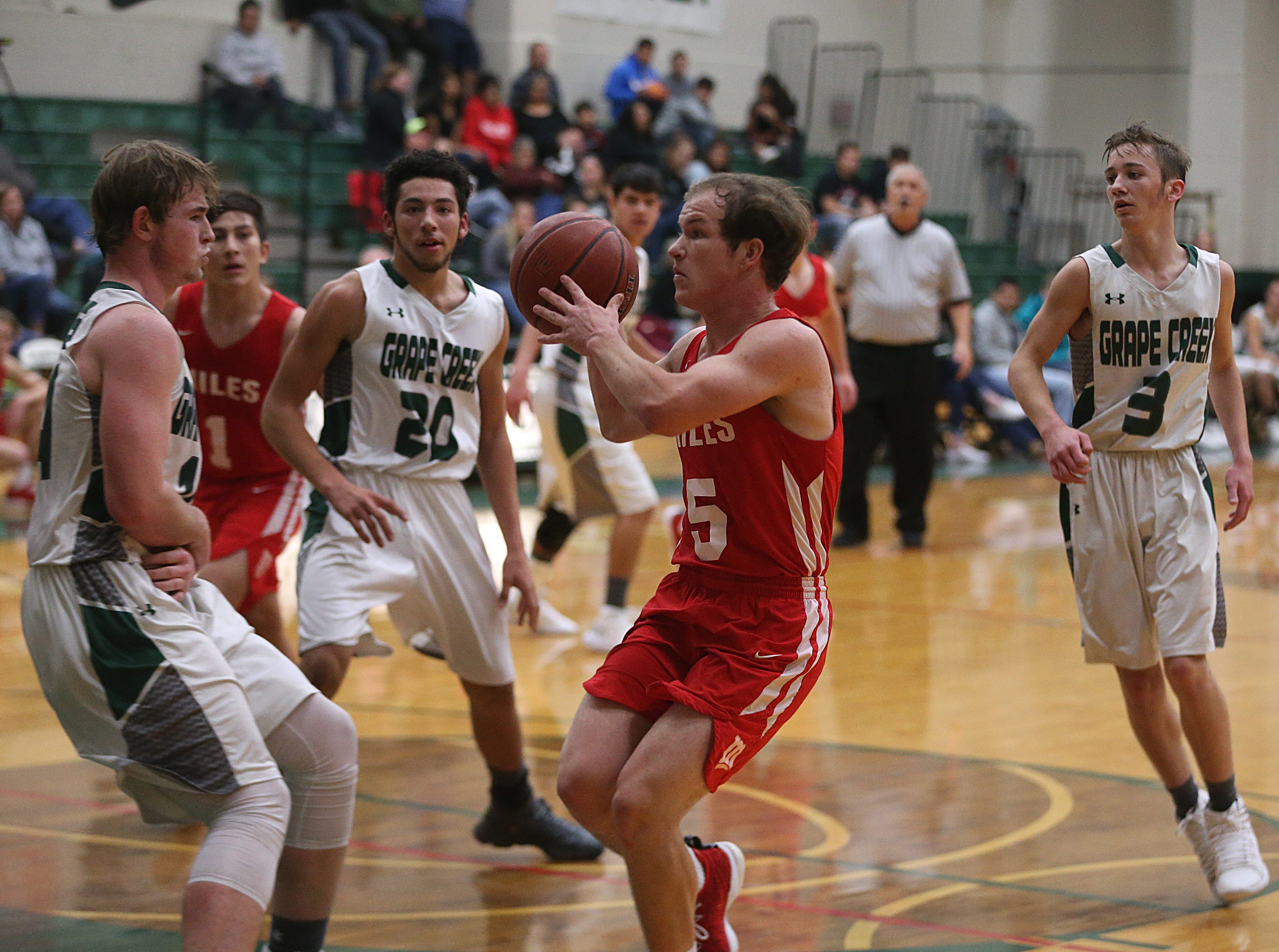 Miles' Mason Bryan (#5) positions himself to shoot the ball Friday, Dec. 14, 2018 during their game against Grape Creek. Miles won 50 to 38.