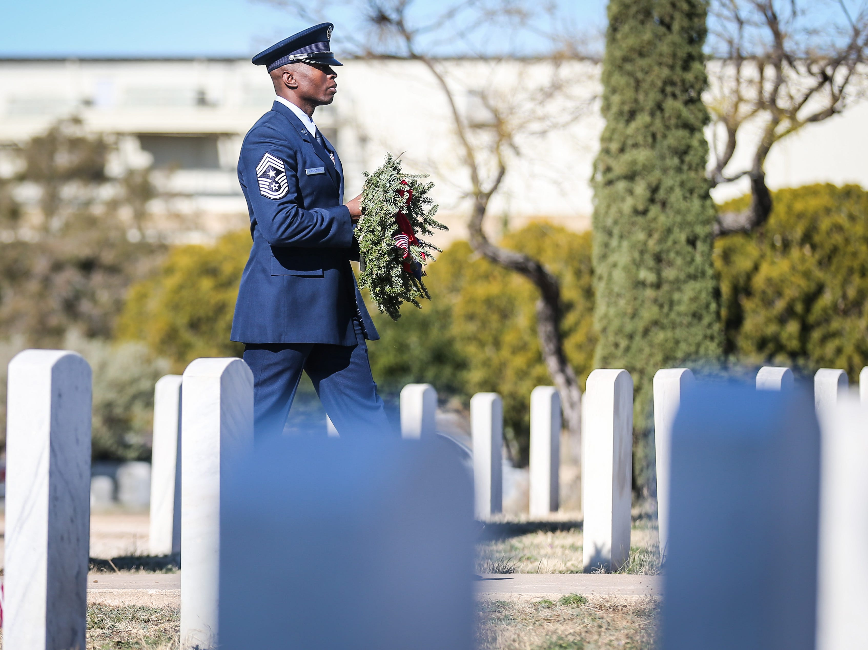 Chief Master Sgt. Labor KirkPatrick, 17th Training Wing at Goodfellow Air Force Base, walks up with a ceremonial wreath during the Wreaths Across America Saturday, Dec. 15, 2018, at Belvedere Memorial Park.