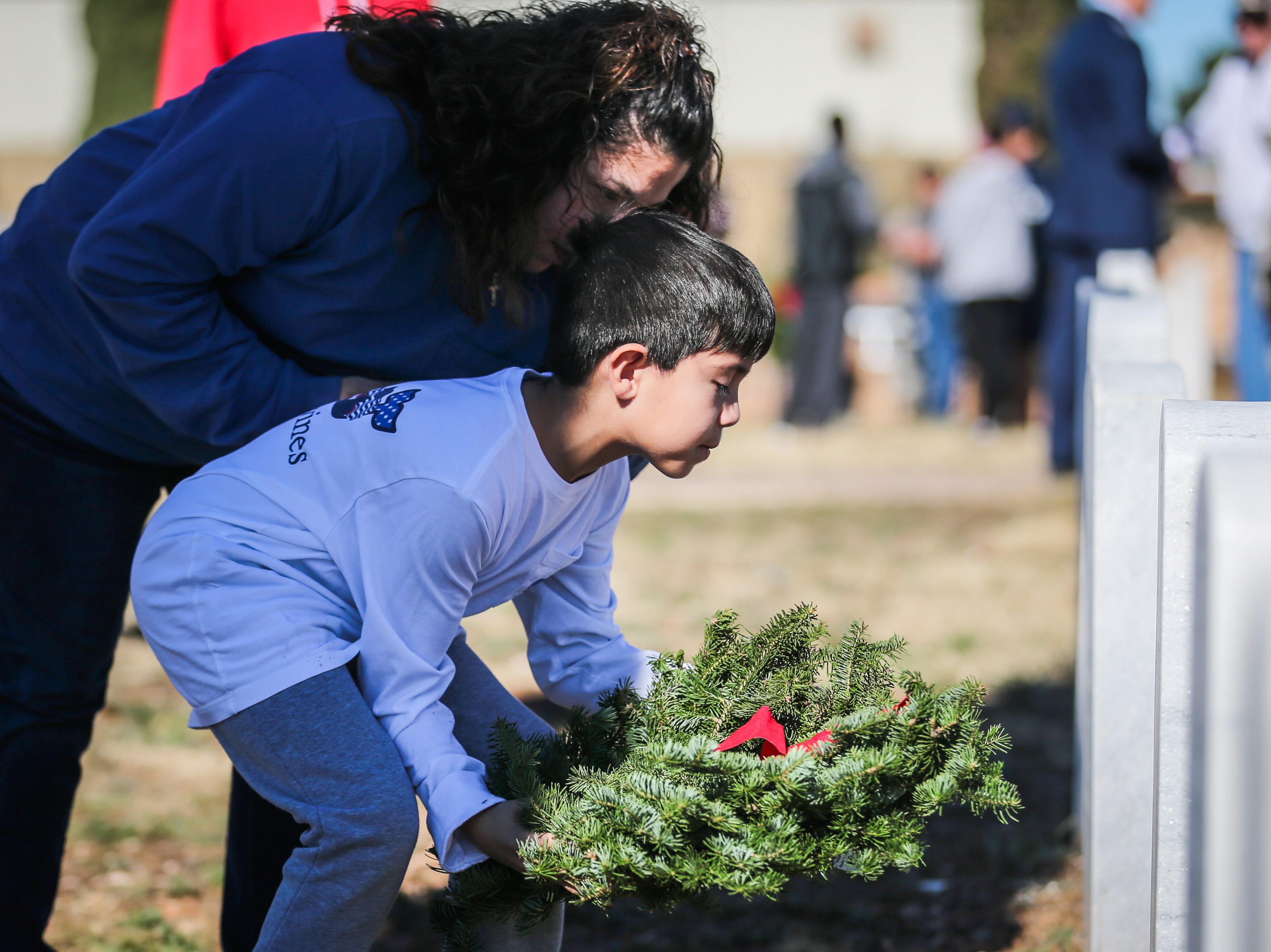 Daisy Seballes Ari Seballes, 8, place a wreath on a grave during Wreaths Across America Saturday, Dec. 15, 2018, at Belvedere Memorial Park.