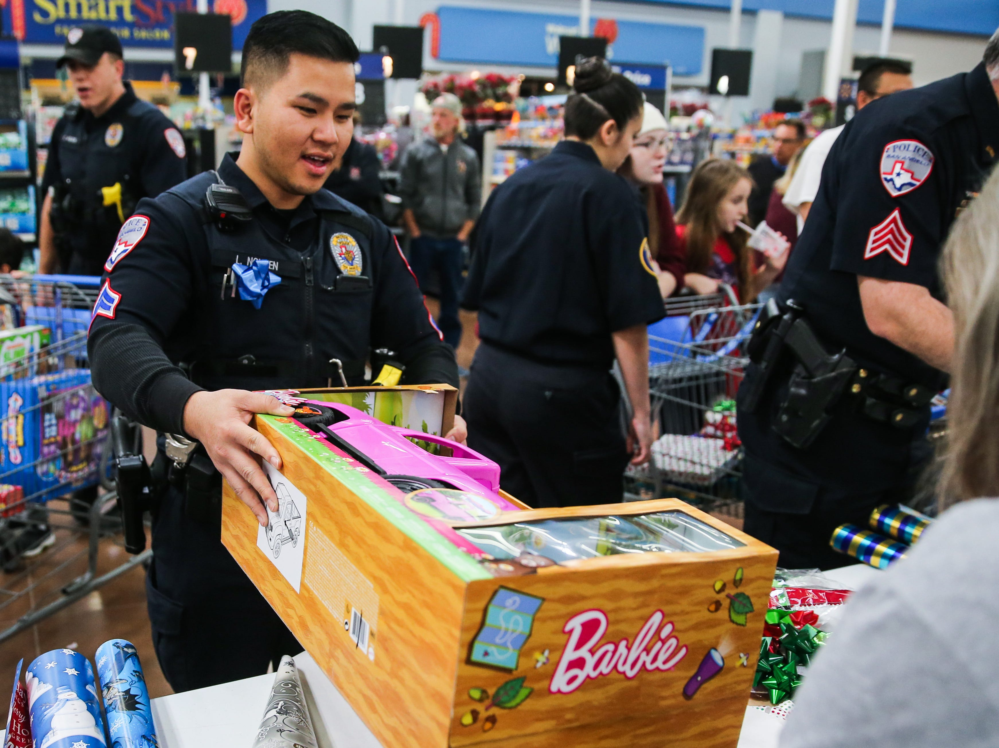 Officer Long Nguyen helps wrap a gift during Shop with a Cop event Saturday, Dec. 15, 2018, at Walmart.