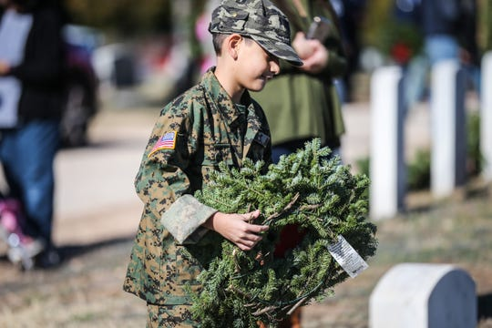 Lee Rosales, 8, places a wreath during Wreaths Across America Saturday, Dec. 15, 2018, at Belvedere Memorial Park.
