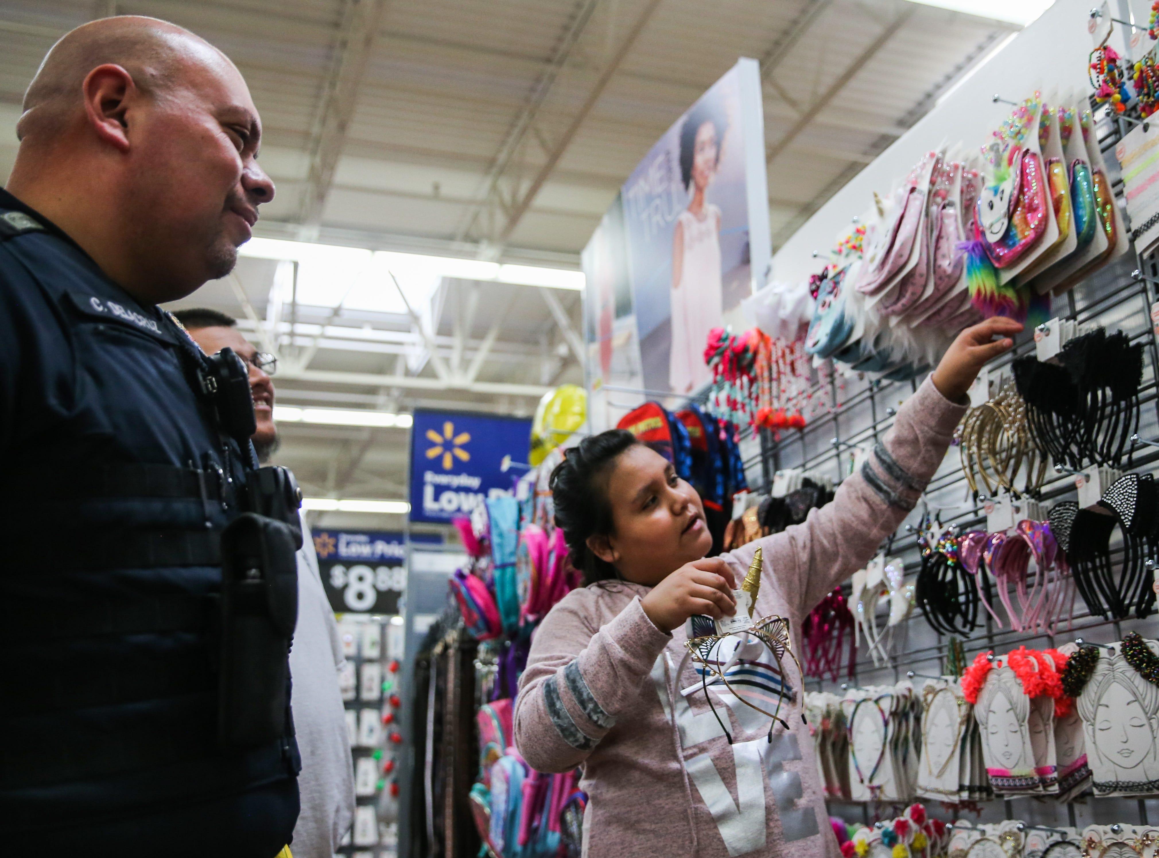 Officer CJ Delacruz watches Ariah Toscano, 9, pick headbands during Shop with a Cop event Saturday, Dec. 15, 2018, at Walmart.