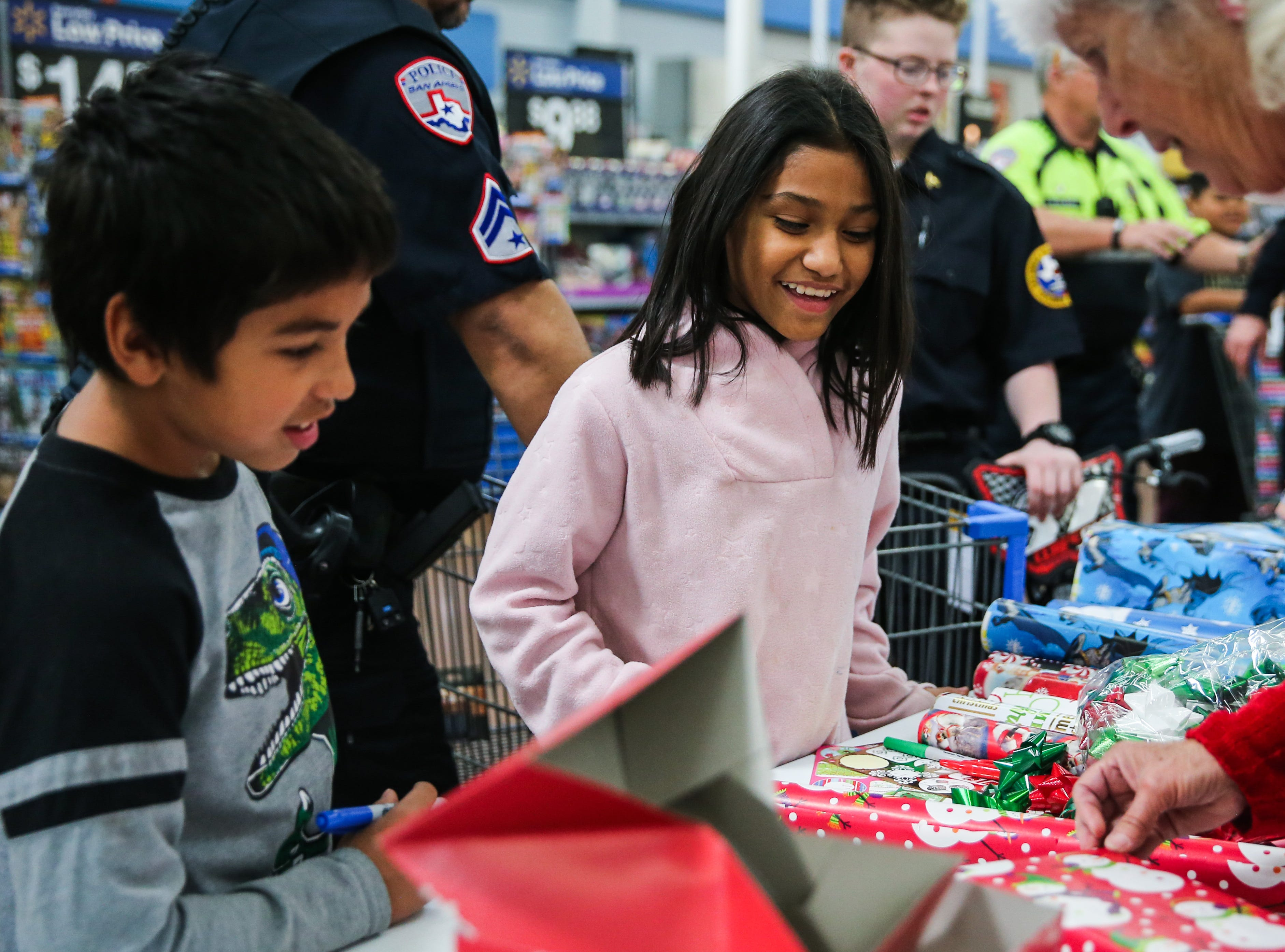 Bradley Borders, 9, and Eva Lopez, 10, pick wrapping paper for gifts they picked during Shop with a Cop event Saturday, Dec. 15, 2018, at Walmart.
