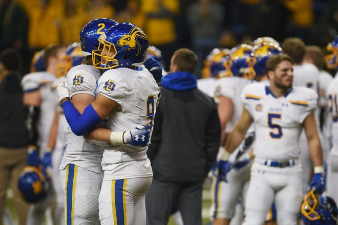 SDSU's Christian Rozeboom, left, and Jordan Brown, right, hug after their lose against NDSU at the Fargodome Friday, Dec. 14, in the FCS playoffs in Fargo.