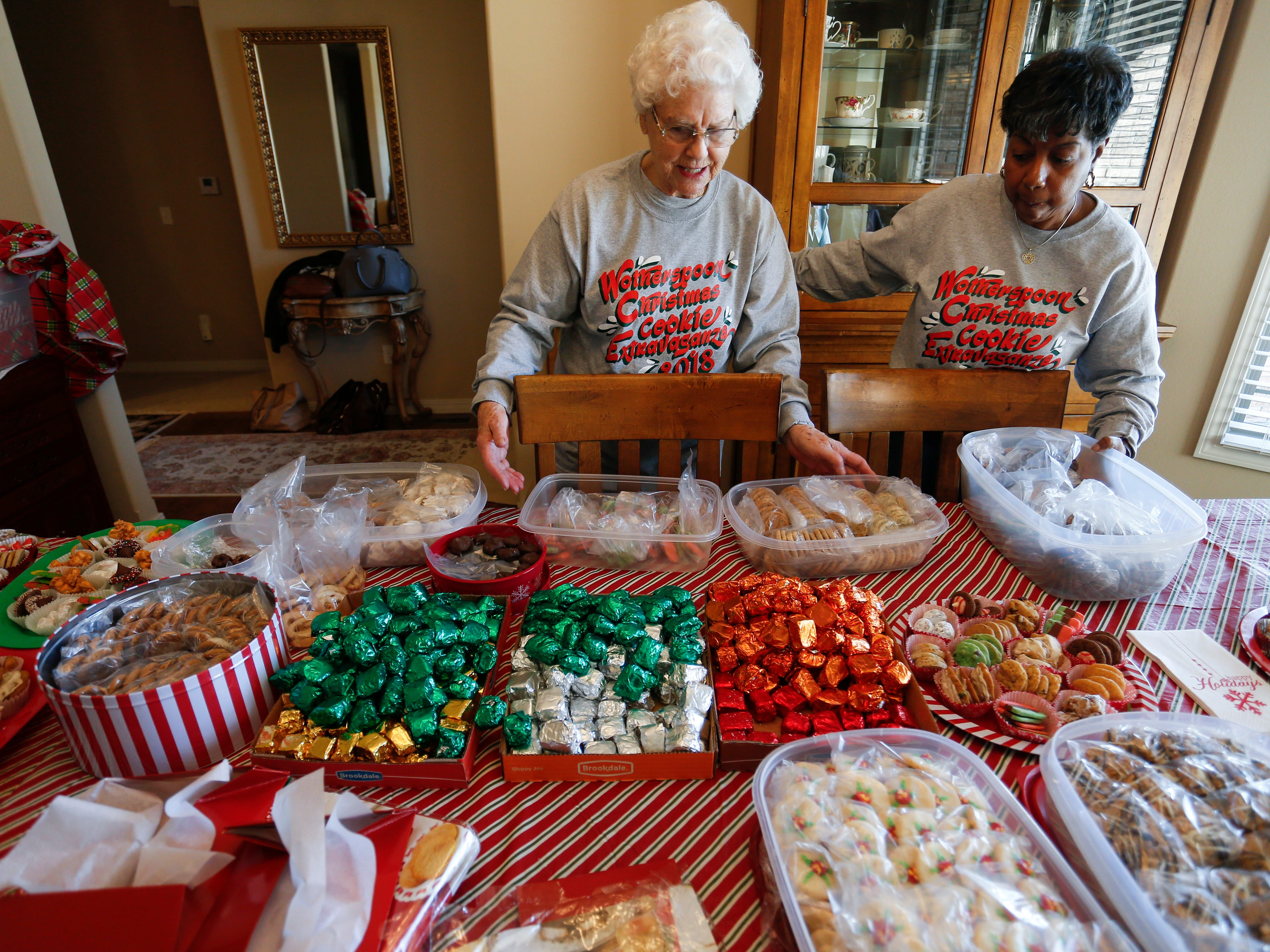 Jeanette Wotherspoon, 84, and cousin Pam Ivy place tubs of Christmas cookies out on the table for the Wotherspoon Christmas cookie extravaganza on Saturday, Dec. 15, 2018.