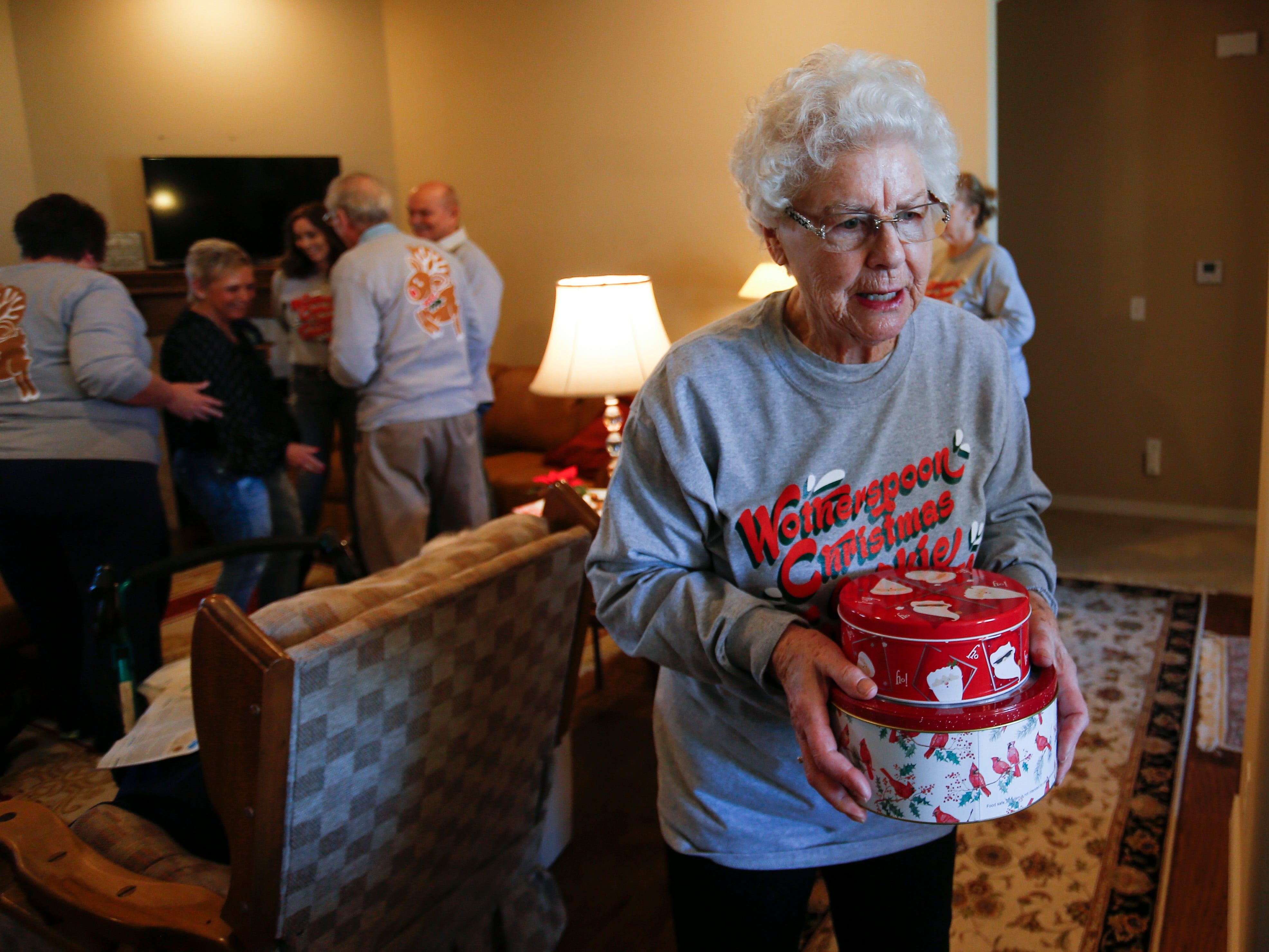Jeanette Wotherspoon, 84, carries tins of cookies for guests at the Wotherspoon Christmas cookie extravaganza on Saturday, Dec. 15, 2018.