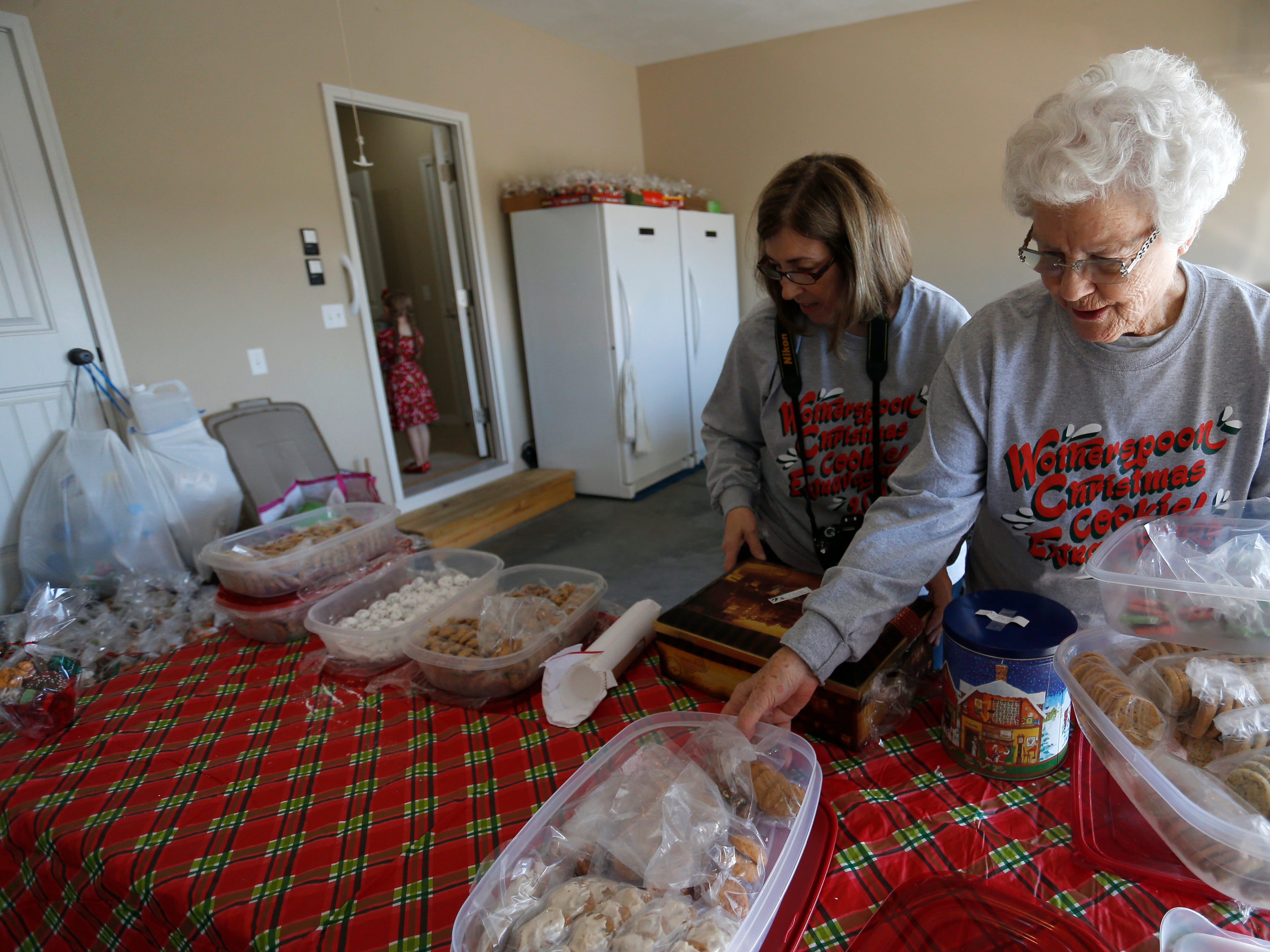 Jeanette Wotherspoon, 84, and daughter Rebecca Wotherspoon move tubs of cookies from the garage into the house as they restock some of the thousands of cookies during the annual Wotherspoon Christmas cookie extravaganza on Saturday, Dec. 15, 2018.
