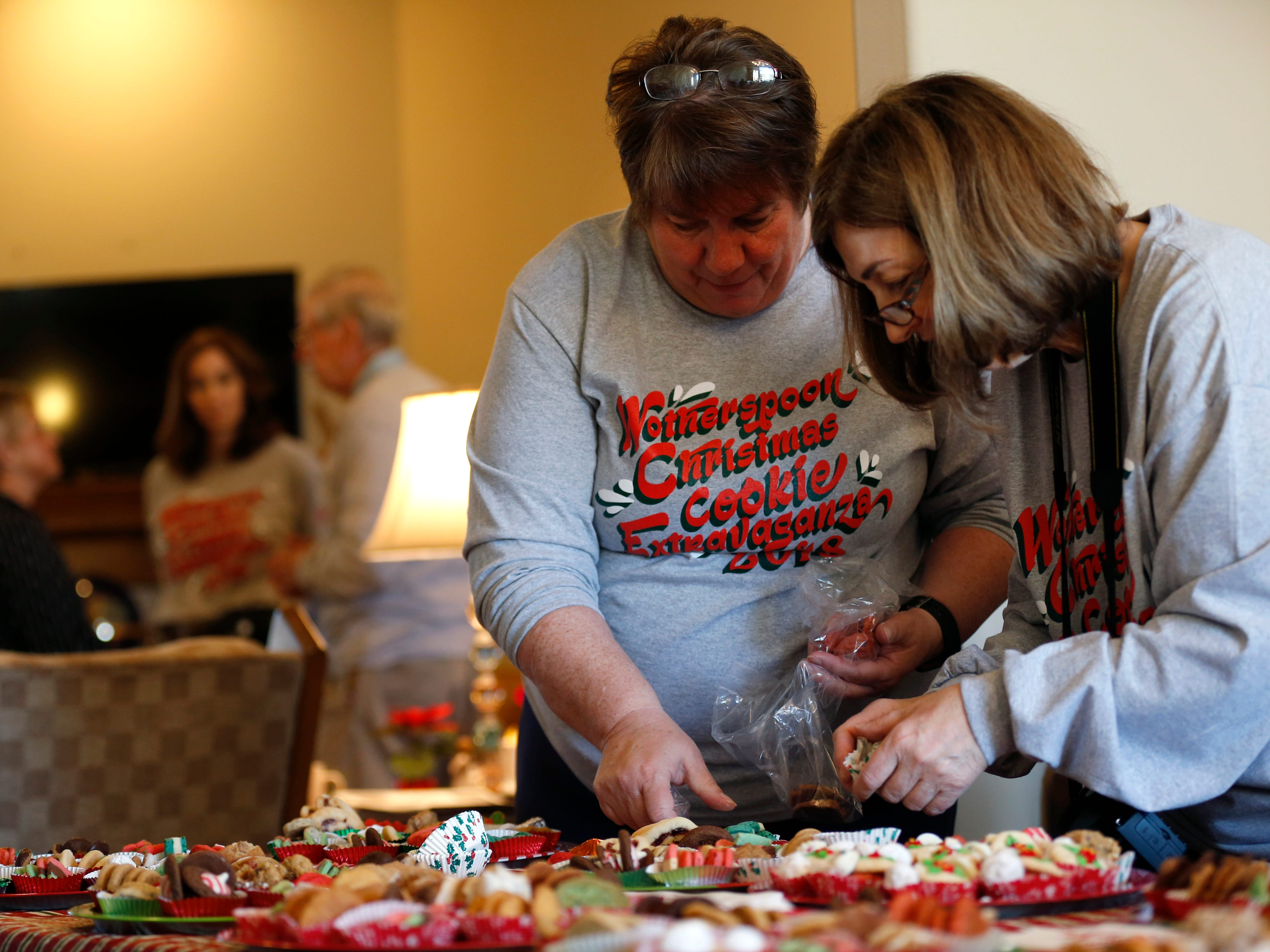 Family friend Sally Hibbs (left) and Rebecca Wotherspoon restock cookies for sampling at the annual Wotherspoon Christmas cookie extravaganza on Saturday, Dec. 15, 2018.
