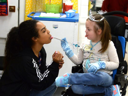 "Ameiya Robinson, a freshman at Robert E. Lee High School, helped Bessie Weller second-grader Lucy Rhoden celebrate Friday during a ""Frozen"" party. Robinson will accompany Rhoden to Disney World as part of a Make-A-Wish trip."