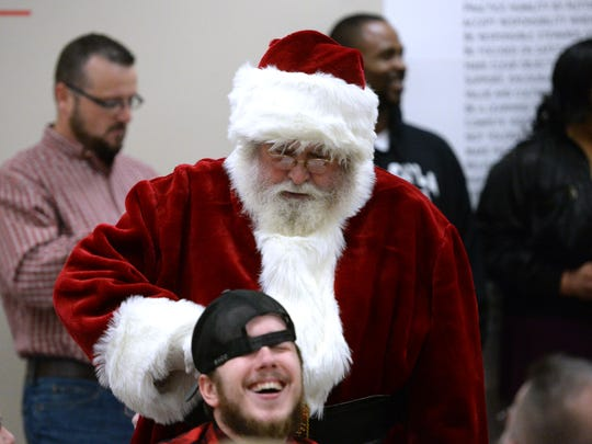 Doug Wright, who has played Santa for more than 30 years, jokes around with an employee of Coca-Cola Bottling at the company's annual Christmas party.