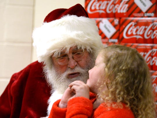 Doug Wright, who has portrayed Santa for more than 30 years, listens to a little girl's wish list at the annual Coca-Cola Bottling Company's Christmas party.