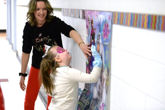 "Second-grade teacher Renee Monger helps Lucy Rhoden play pin the nose on Olaf during her ""Frozen"" party Friday at Bessie Weller Elementary School in Staunton."