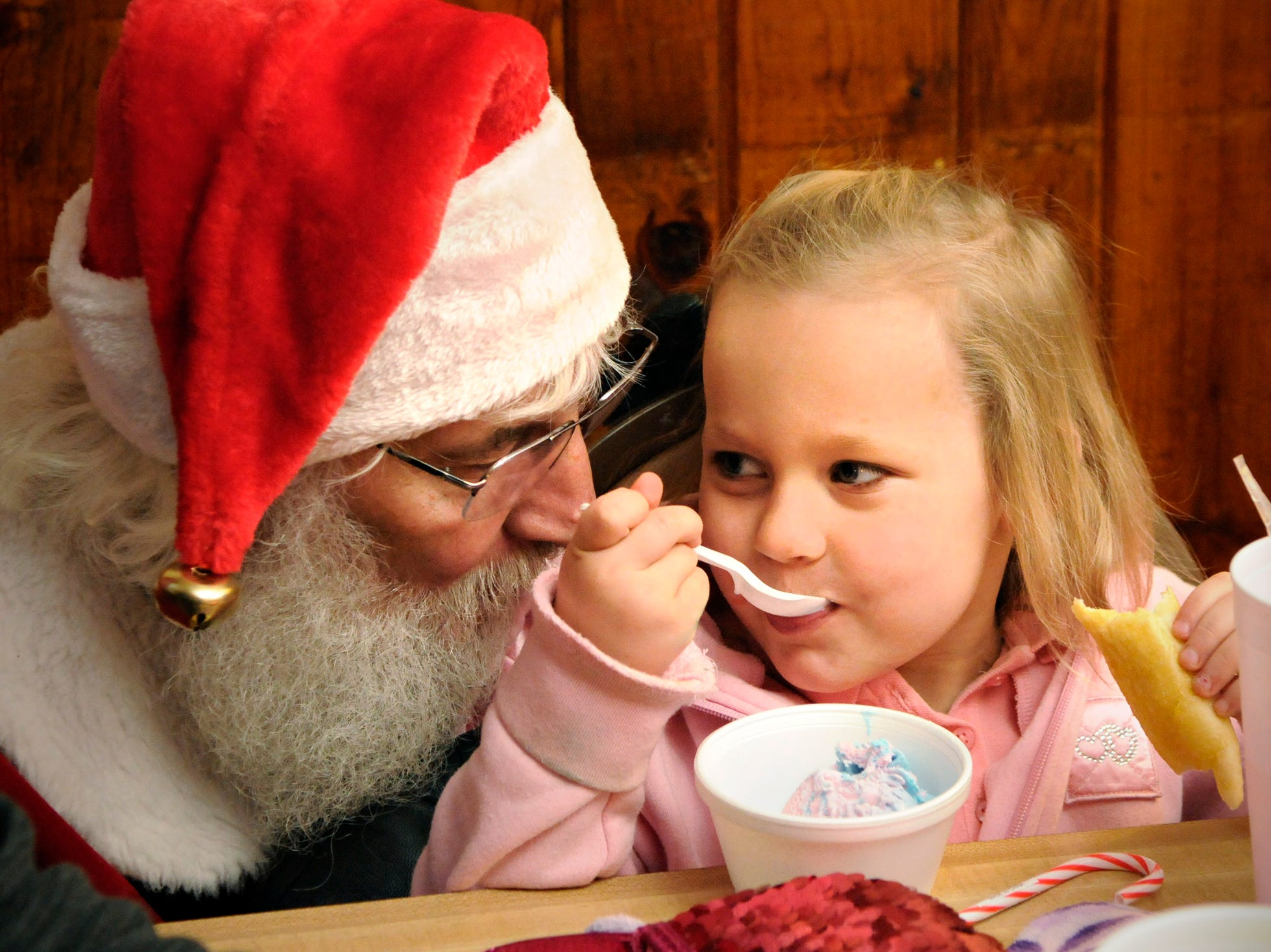 Lilly Prozinski, 4, Upasla, talks with Santa as she eats ice cream and nibbles a bread stick at Charlie's Pizza in Little Falls Tuesday, Dec. 25, 2012. Owner Charlie Peterka opened his restaurant and served free pizza to anyone who did not have holiday plans.